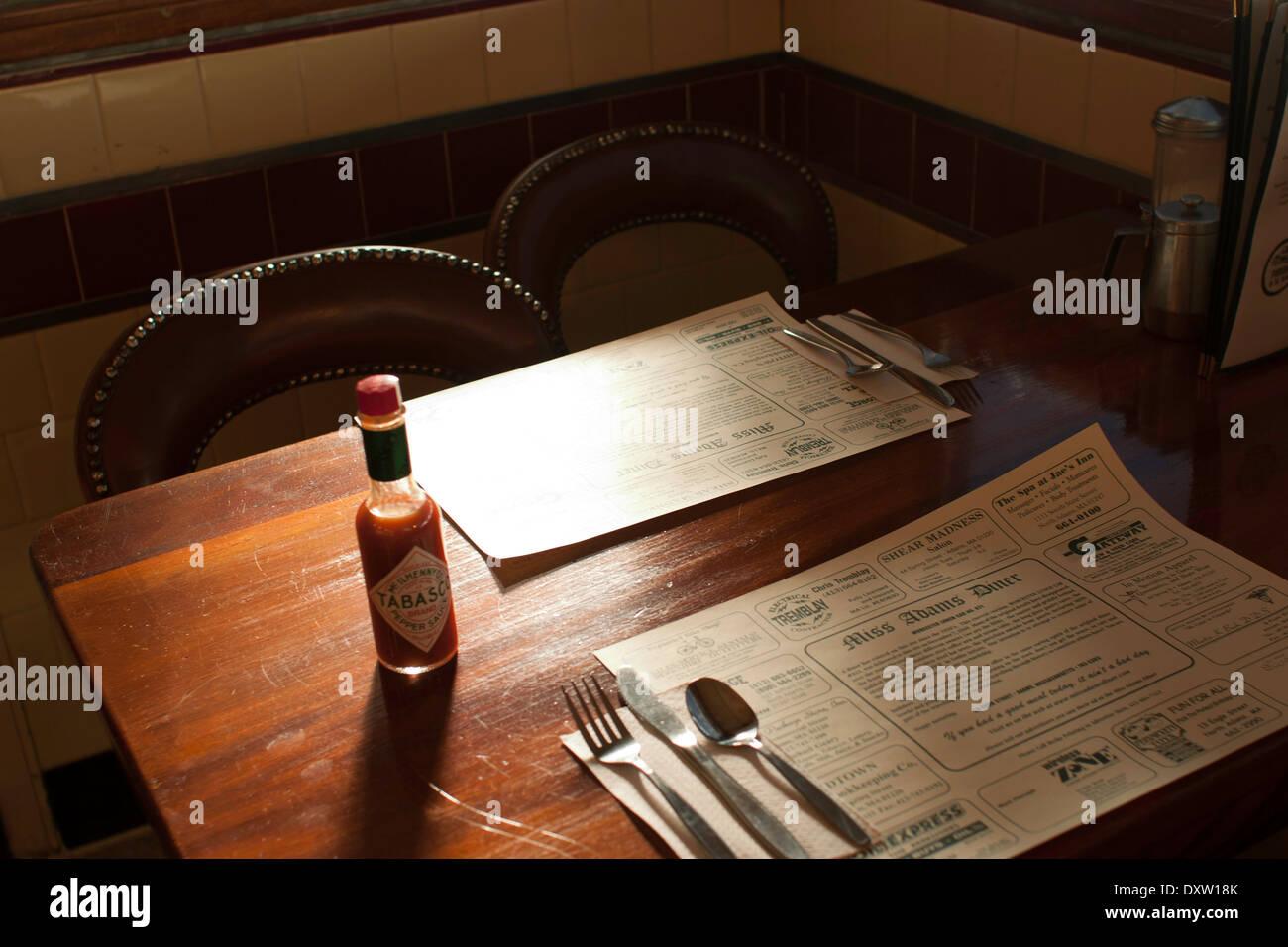 Diner Gewürze sitzen auf dem Tisch in einem Kleinstadt-Diner.  Tischsets werben lokale Unternehmen. Stockbild