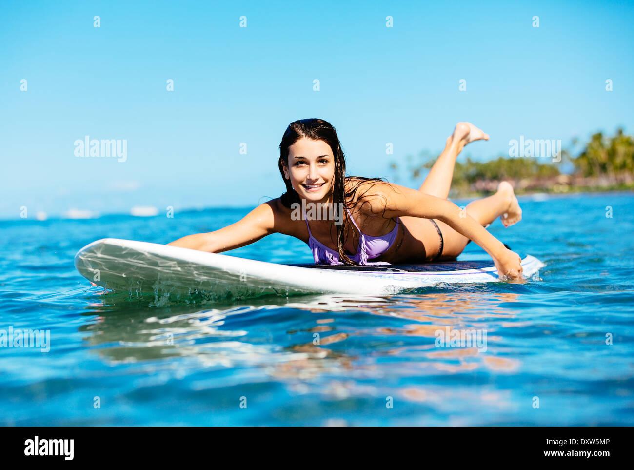 Attraktive junge Frau Surfen auf Hawaii, Paddeln zum Lineup Stockfoto