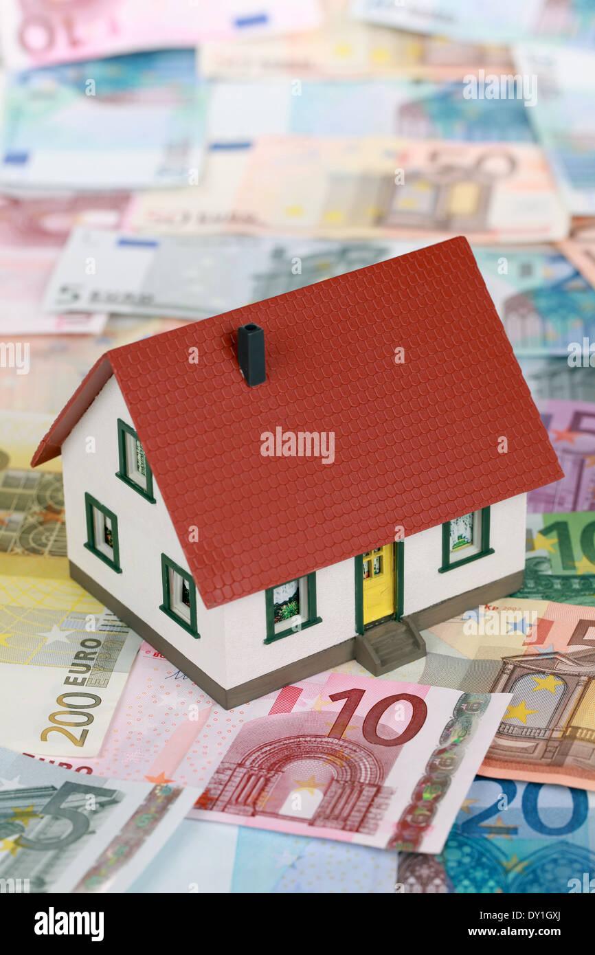 Symbolisches Bild für Immobilienfinanzierungen mit einem Gebäude auf Euro-Banknoten Stockbild
