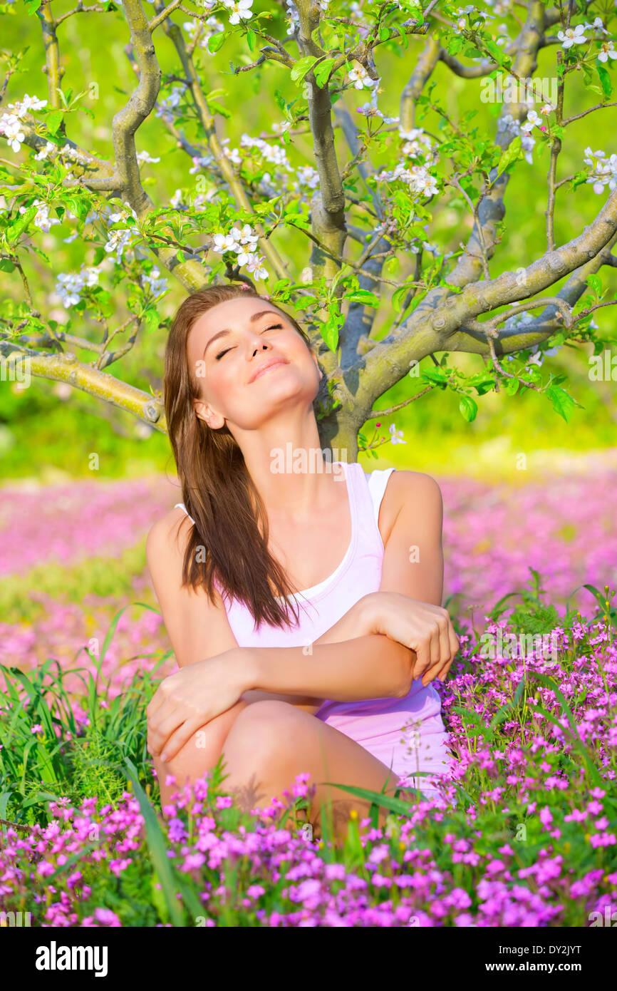 Porträt von schönen ruhigen Mädchen mit geschlossenen Augen sitzen auf pink floral Waldwiese unter Stockbild