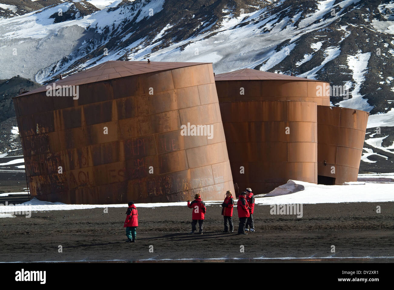 Antarktis Tourismus Whaler es Bay, Deception Island. Touristen aus Kreuzfahrtschiff entdecken Sie in der Nähe von verfallenen Wal Öltanks auf Strand. Stockbild