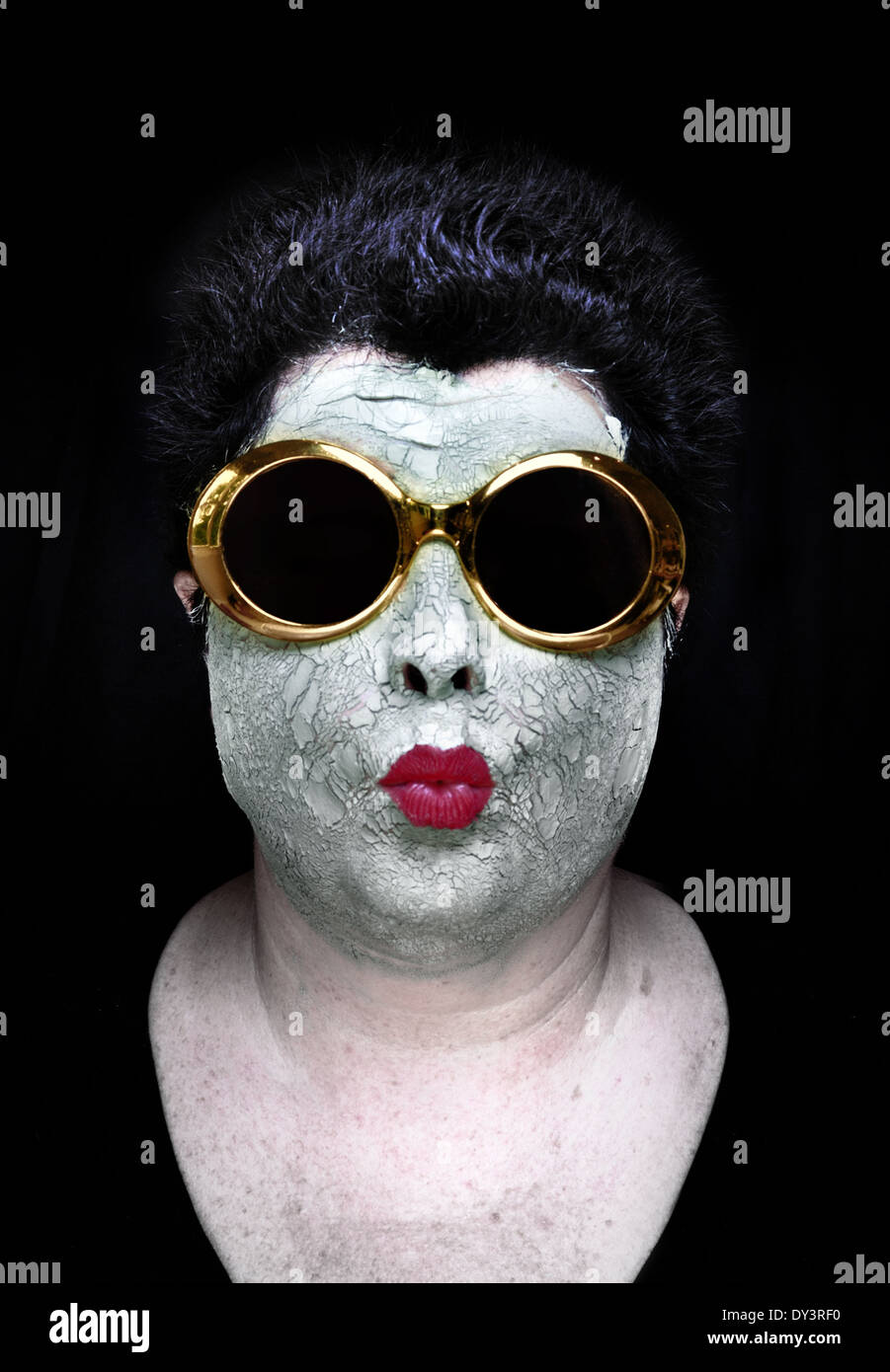 Eine Frau trägt einen grünen Schlamm-Maske, Falten roten Lippenstift und skurrilen gold Sonnenbrille Lippen Stockfoto
