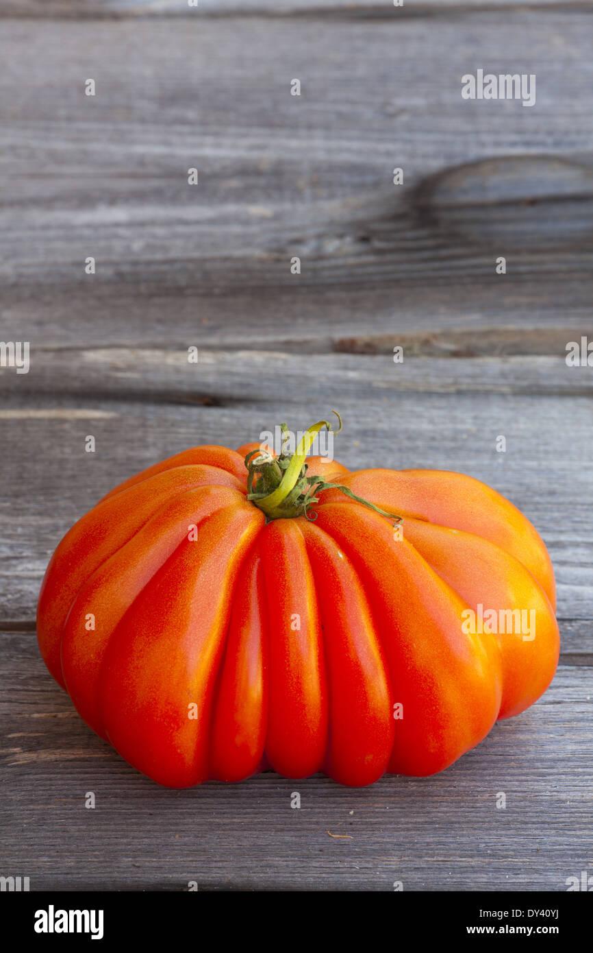 Eine große Beefsteak Tomaten frisch vom Wochenmarkt auf einem alten Holztisch Stockbild