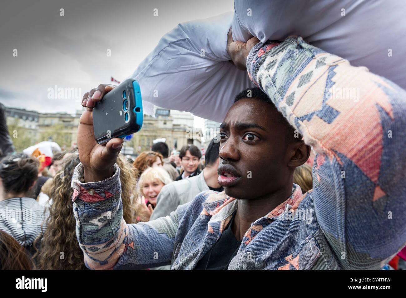 Ein besorgt aussehender Mann dabei, International Pillow Fight Day teilnehmen. Stockbild