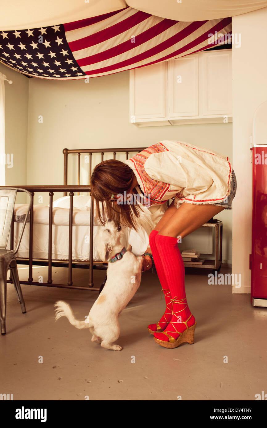 Frau mit roten kniehohen Socken biegen in Richtung Hund Stockbild