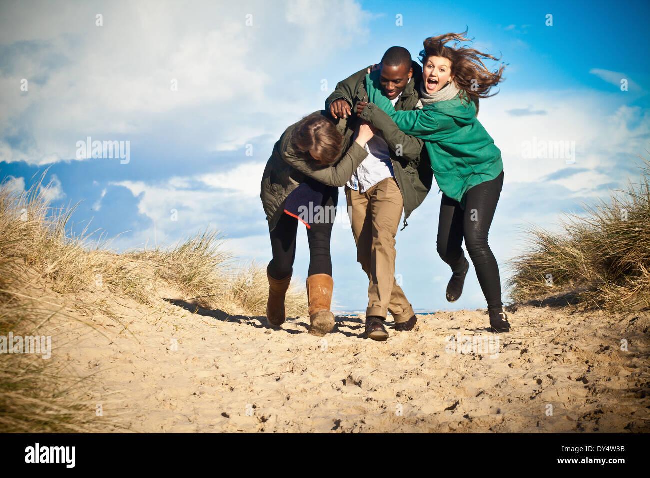 Junge Erwachsene Freunde laufen in Sanddünen, Bournemouth, Dorset, Großbritannien Stockbild