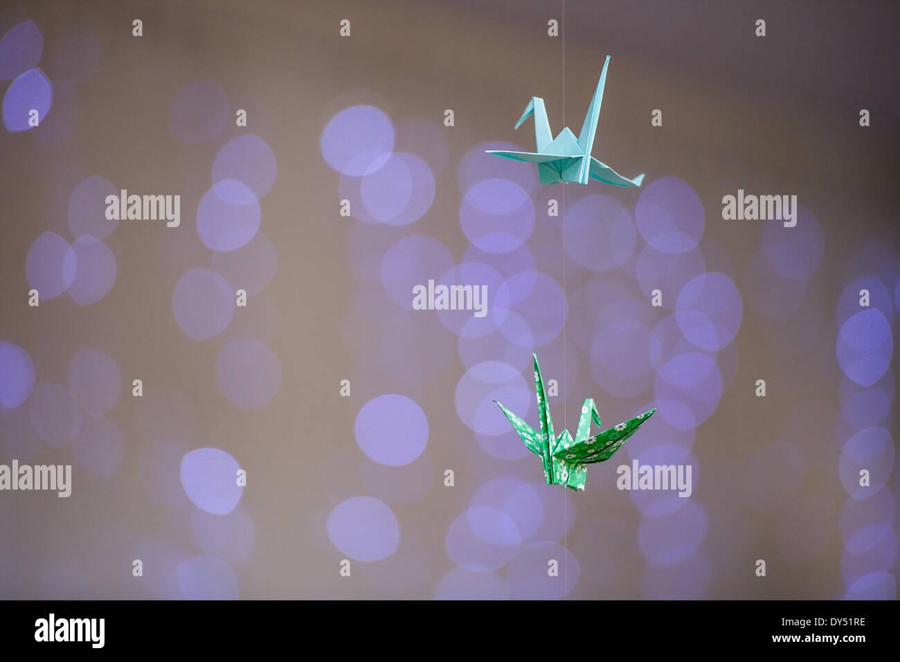 Kraniche aus Origamipapier hängen von der Decke mit Lichterketten in den Hintergrund. Stockbild