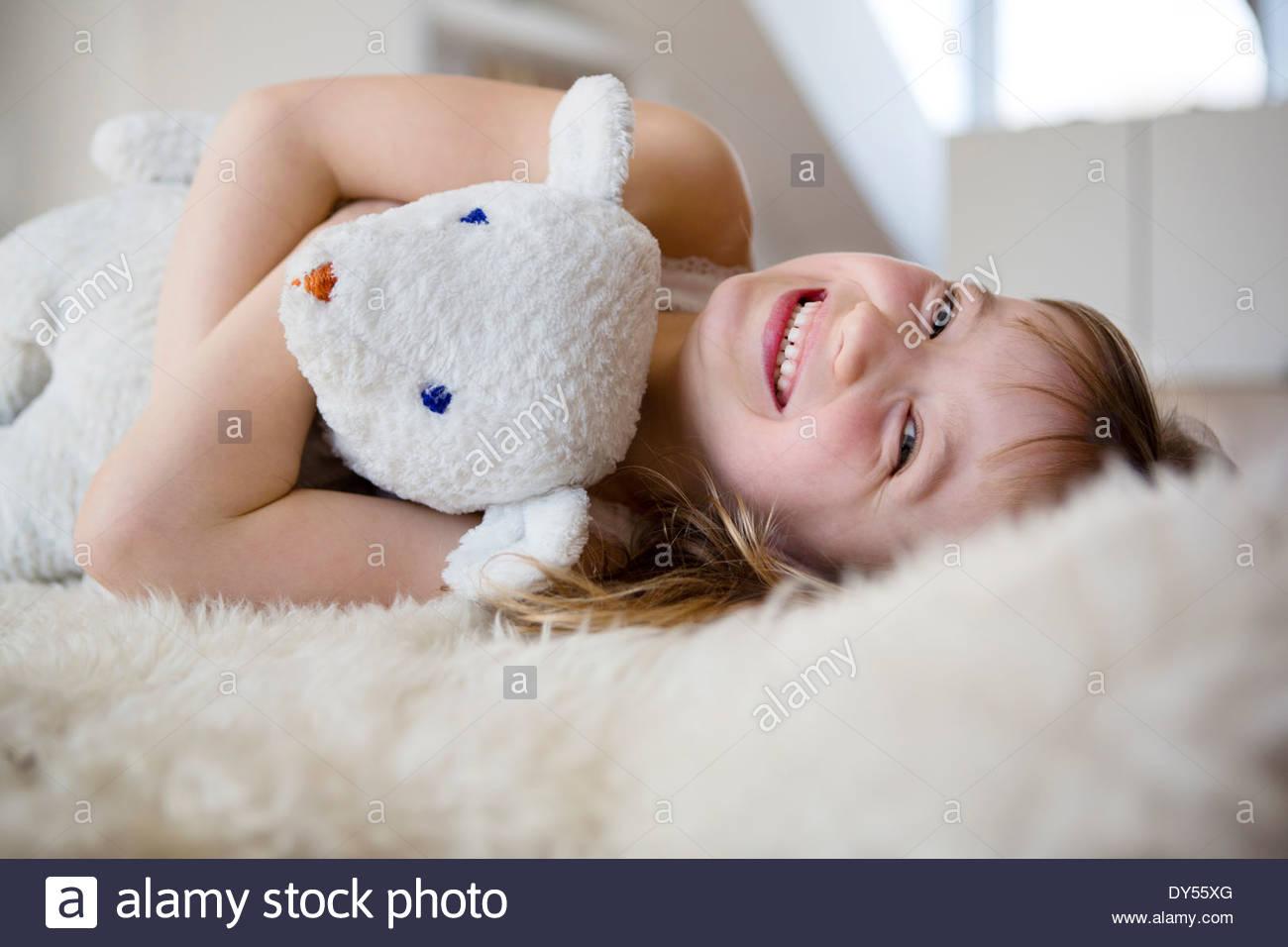 Mädchen auf pelzigen Bett kuscheln Teddybär Stockfoto