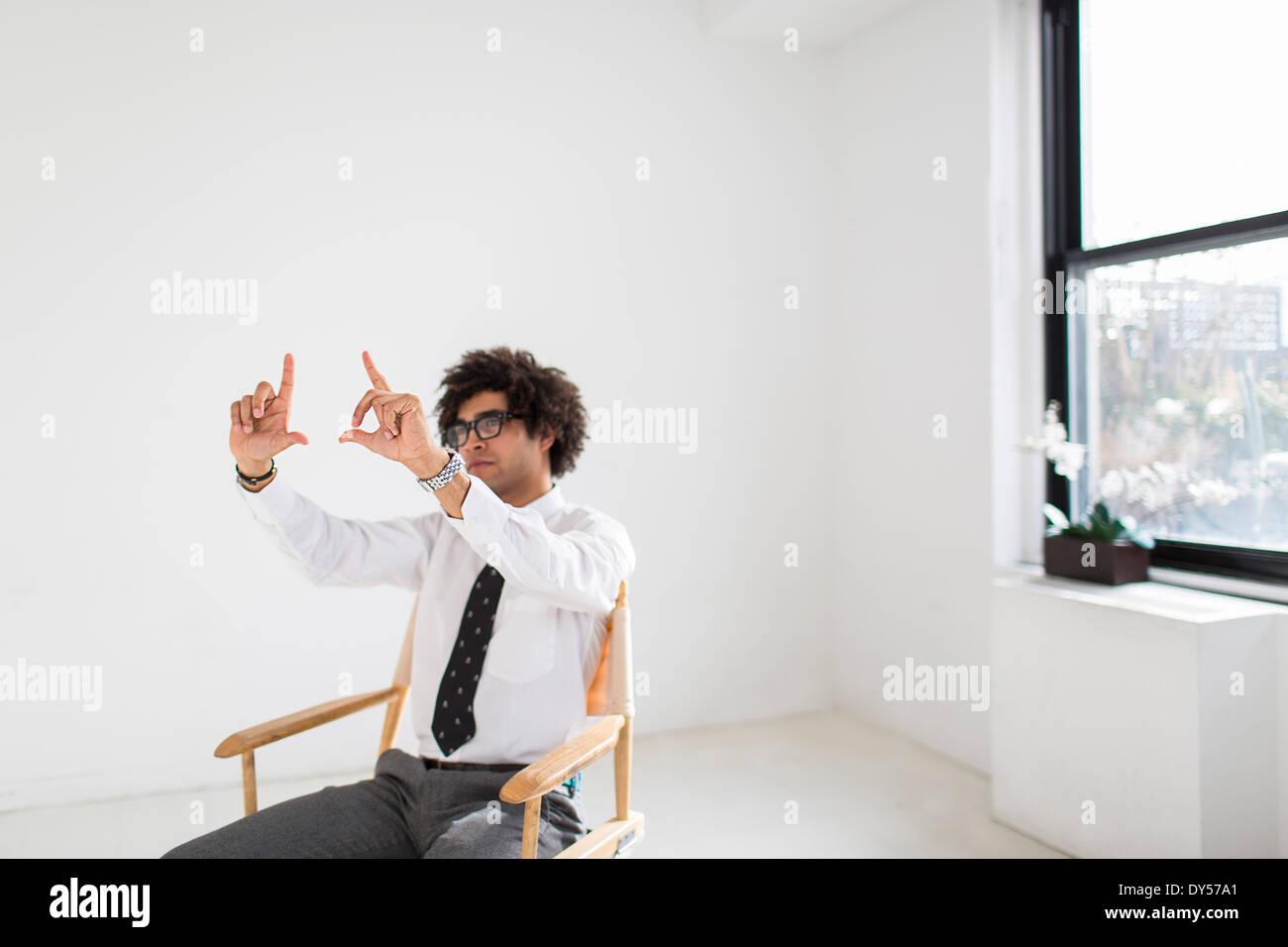 Junger Mann sitzend auf Stuhl macht Finger-frame Stockbild