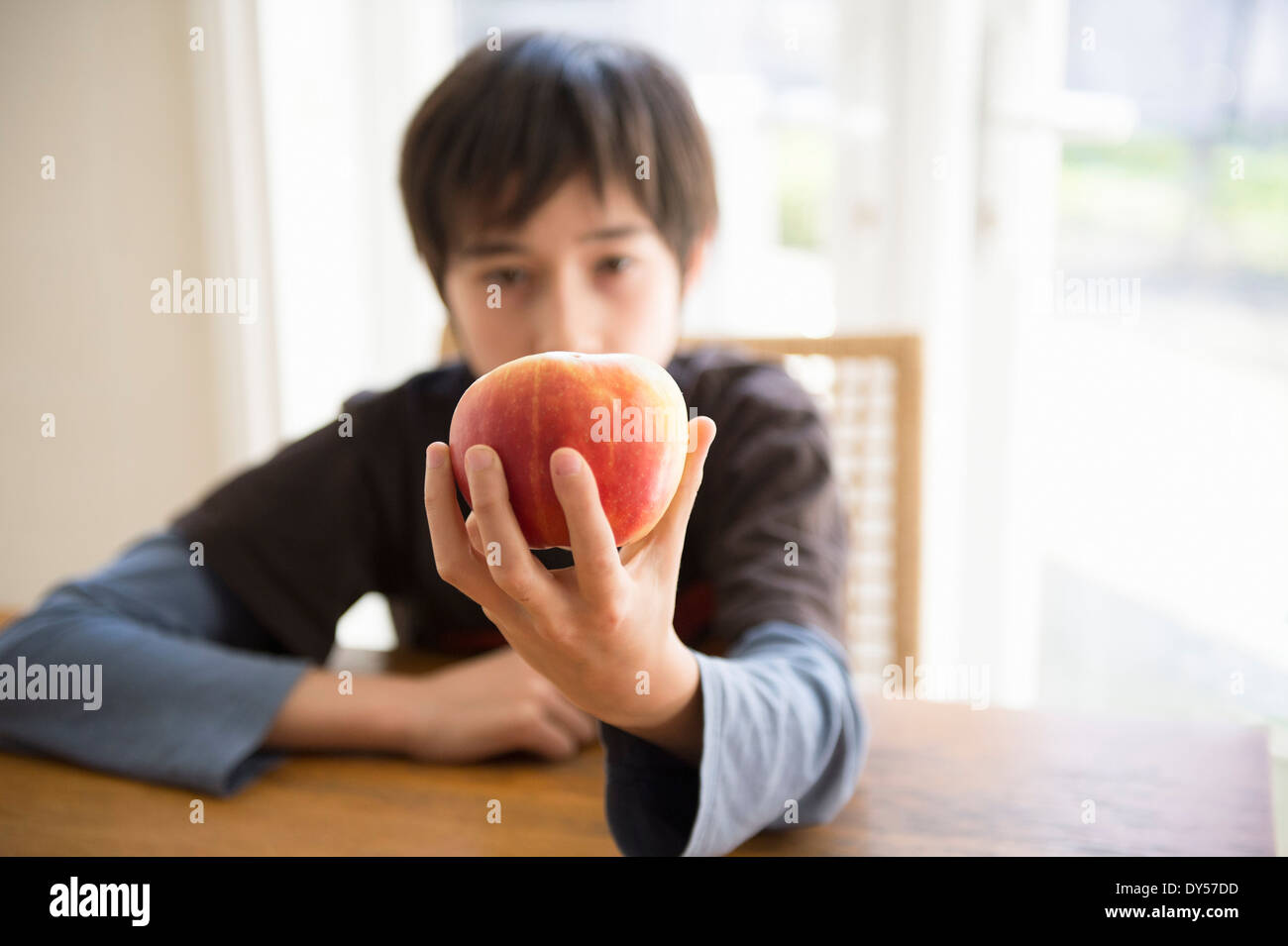 Junge sitzt am Tisch, hält Apfel vor ihm Stockbild