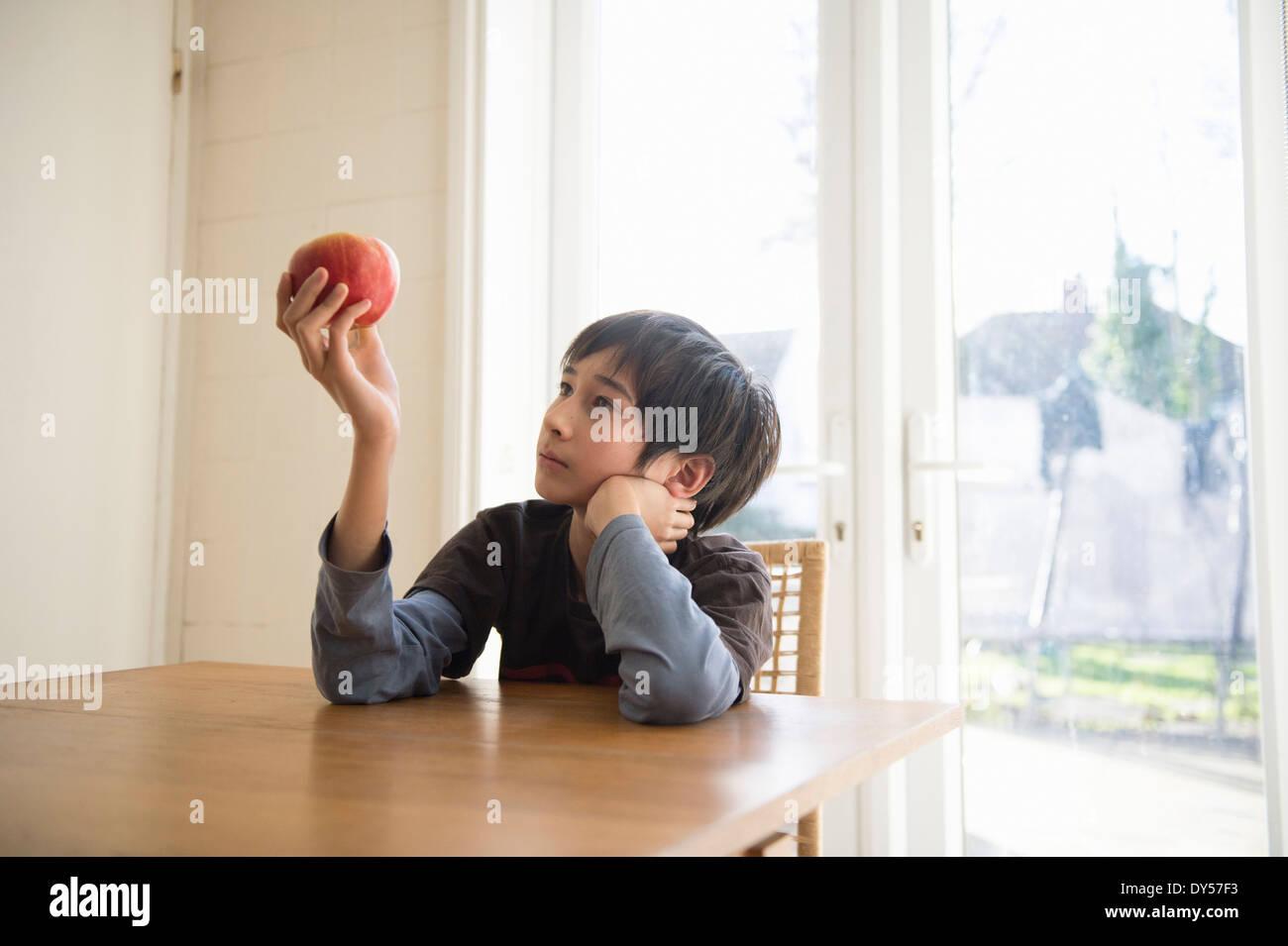 Junge sitzt am Tisch, hält einen Apfel vor ihm Stockbild
