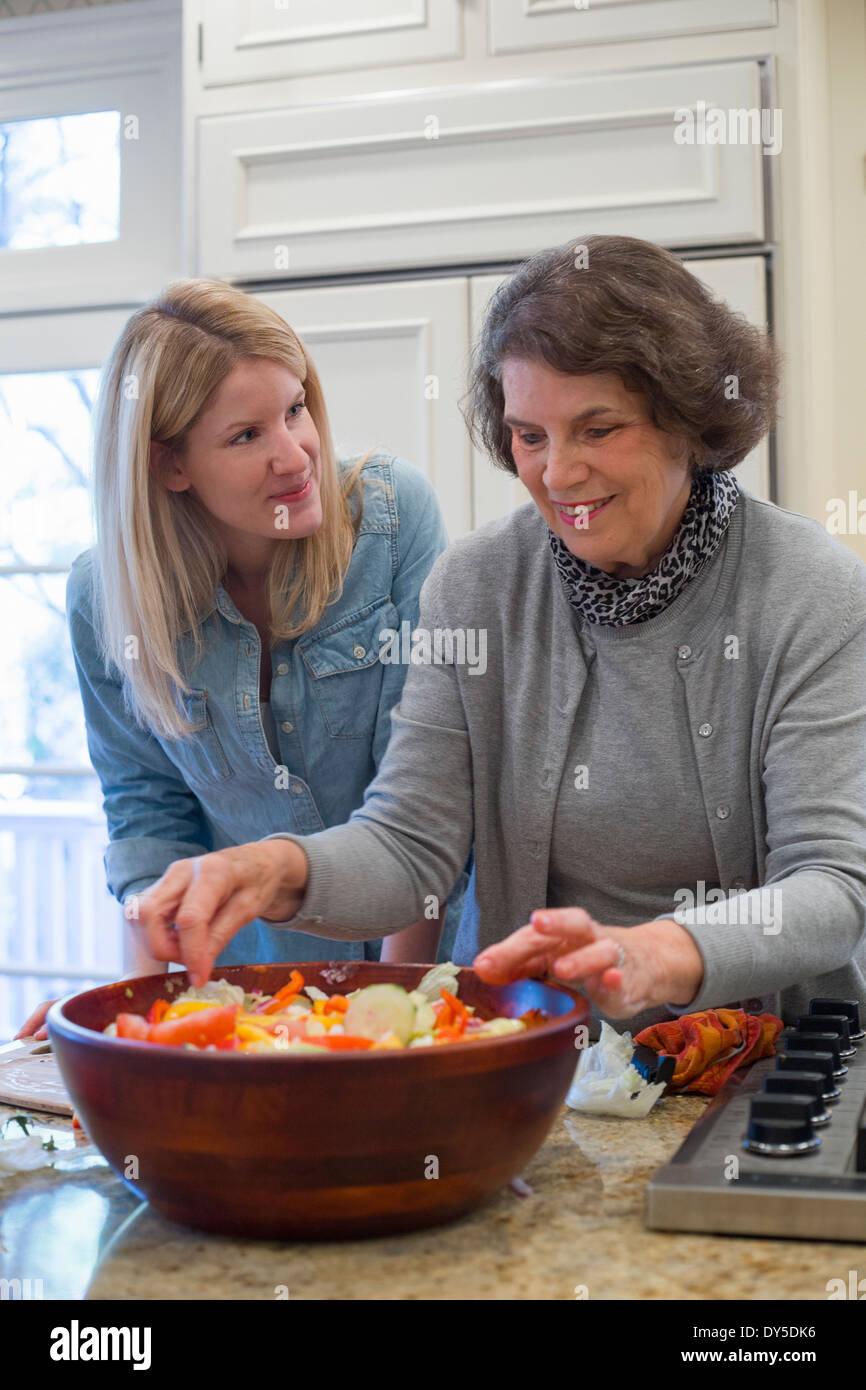 Ältere Frau und Enkelin Vorbereitung Salatschüssel Stockbild