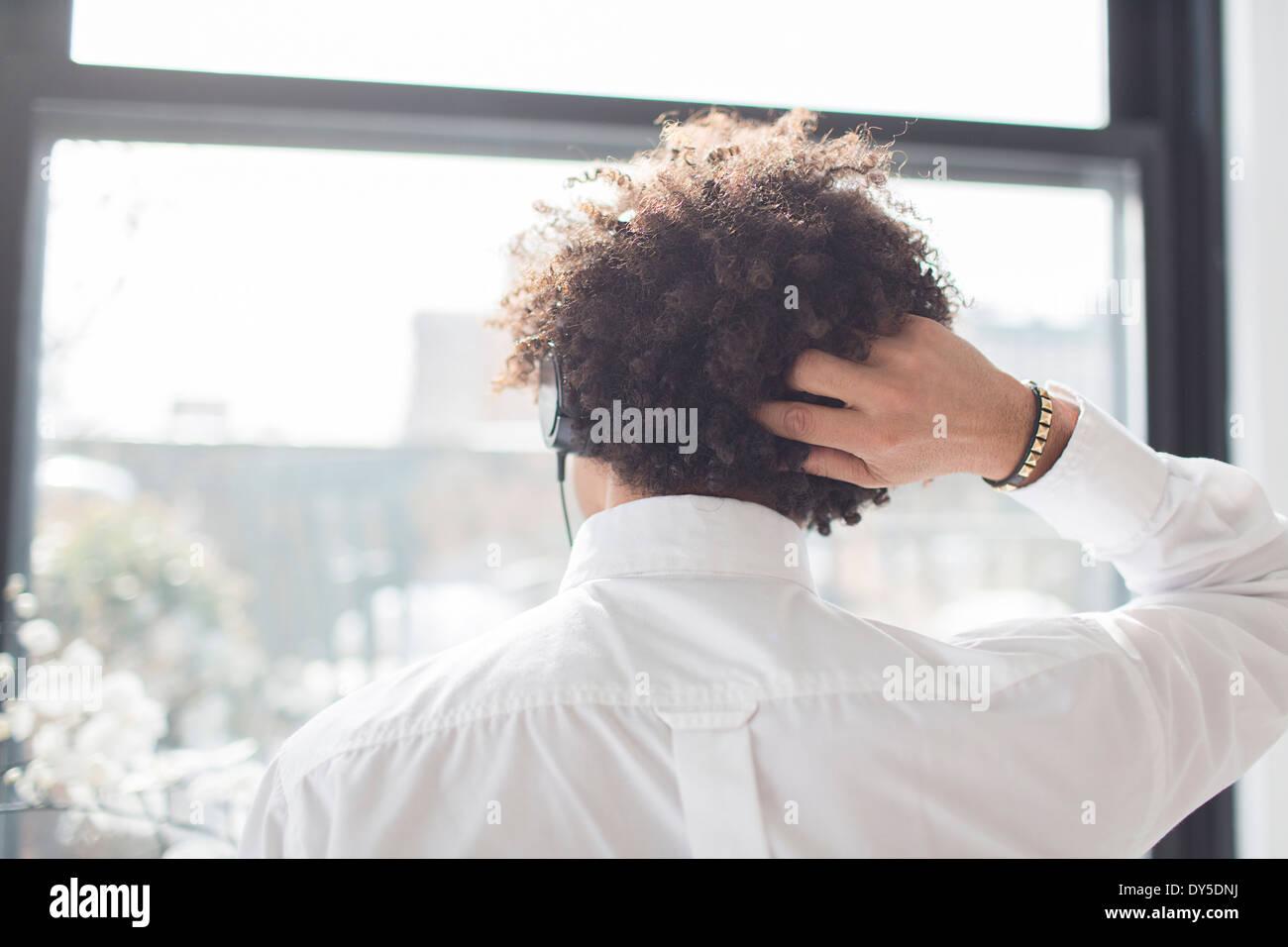 Junger Mann kratzen Kopf, Rückansicht Stockbild