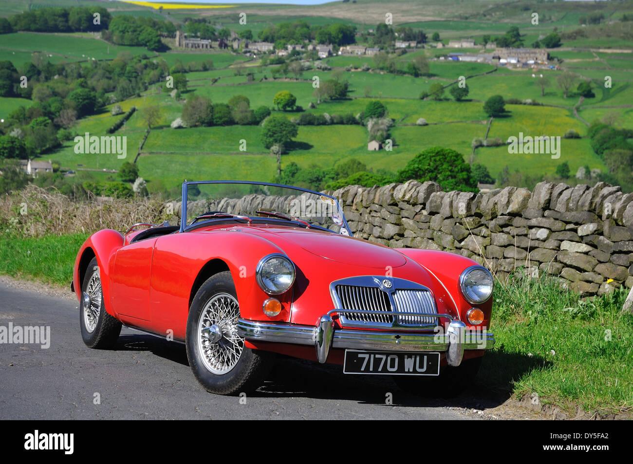 Ein MGA-Sportwagen steht auf einem Feldweg im Sommer mit einem englischen Dorf auf dem Hügel im Hintergrund Stockbild