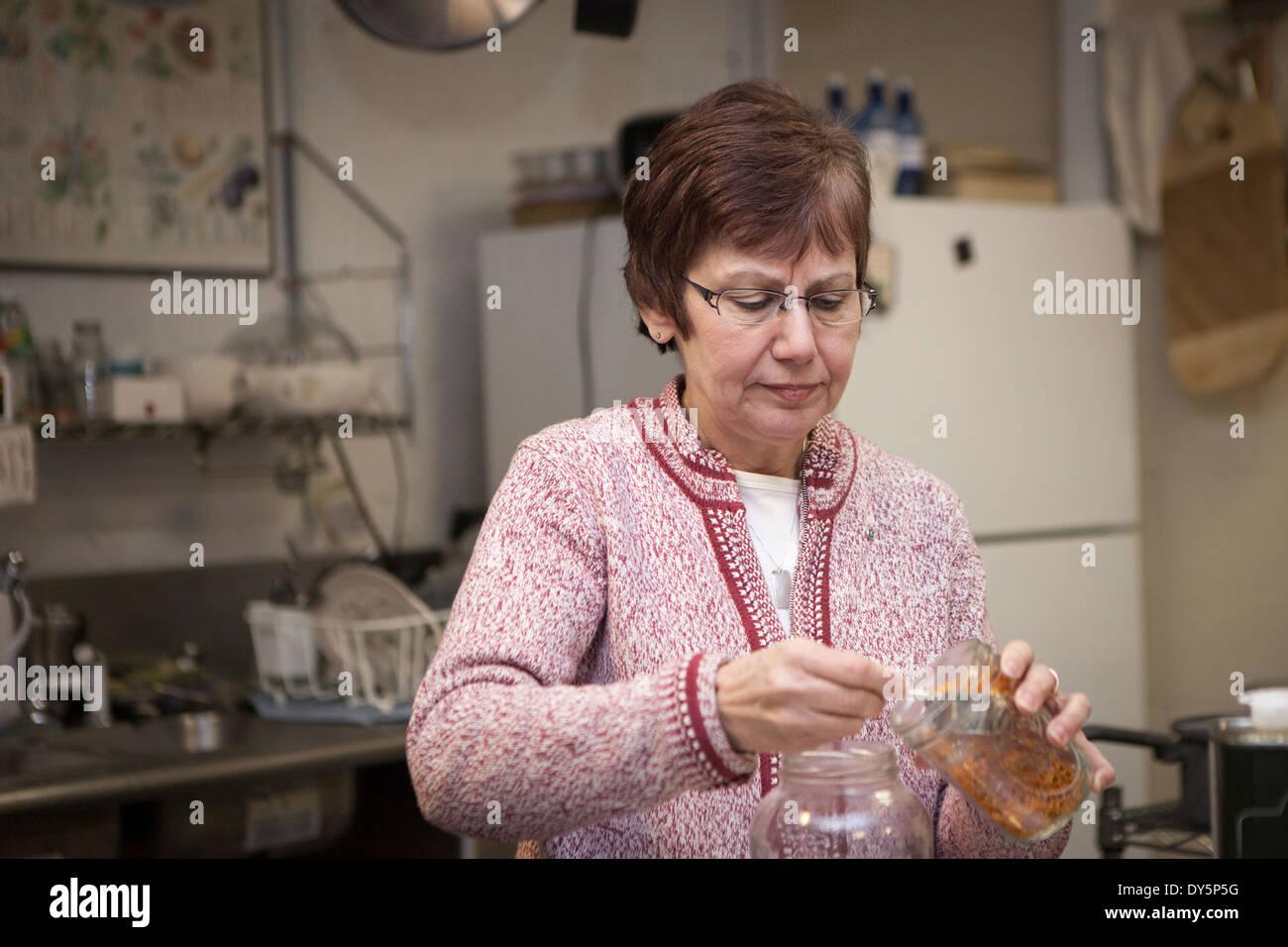 Gesunde Lebensmittel-Shop-Besitzer setzen Kräuter in Gläsern Stockbild