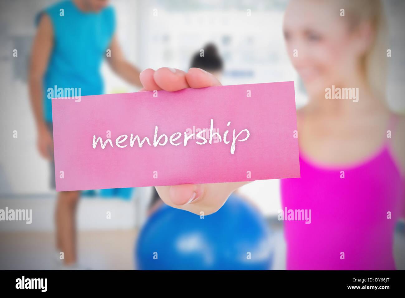 Fit Blondine hält Karte Spruch Mitgliedschaft Stockfoto