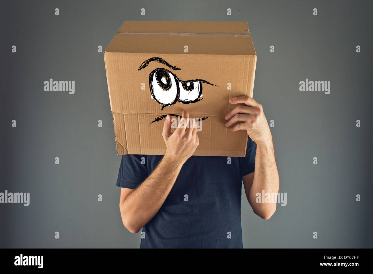 Mann mit Karton auf den Kopf mit ernsten Gesichtsausdruck zu denken. Stockbild
