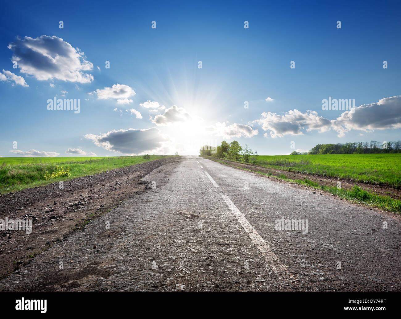 Asphaltierte Highway in das Feld und Sonnenlicht Stockbild