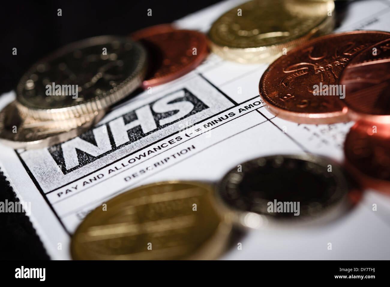 NHS Haushaltskürzungen Konzept - eine generische NHS Gehaltsabrechnung Lohn-oder Gehaltsabrechnung mit britischen Münzen des Reiches erschossen auf einem schwarzen Hintergrund Stockbild
