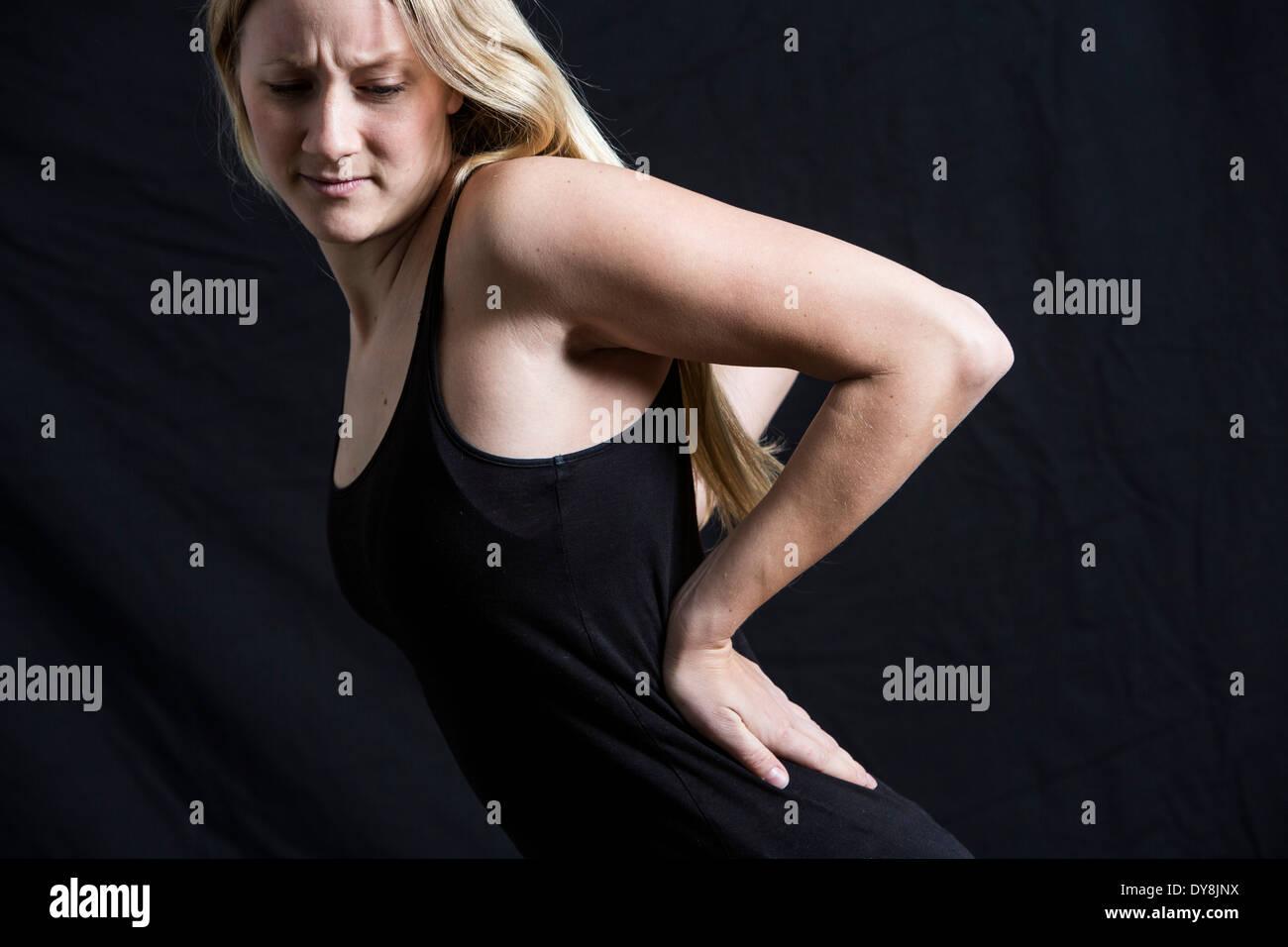Junge Frau hat Rückenschmerzen Stockbild