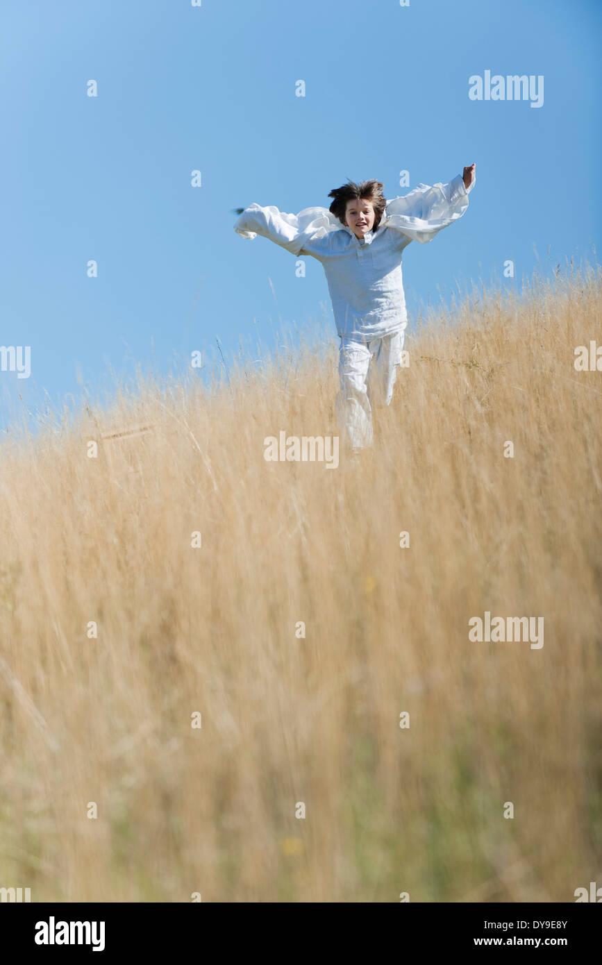 Junge läuft durch hohe Gräser Stockbild
