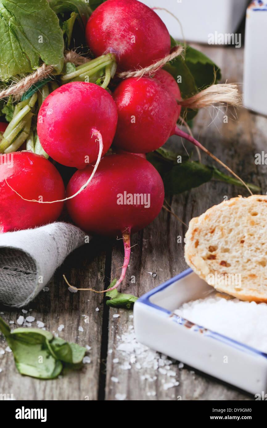 Frisches nass Radieschen mit Salz und Brot über alten Holztisch Stockfoto