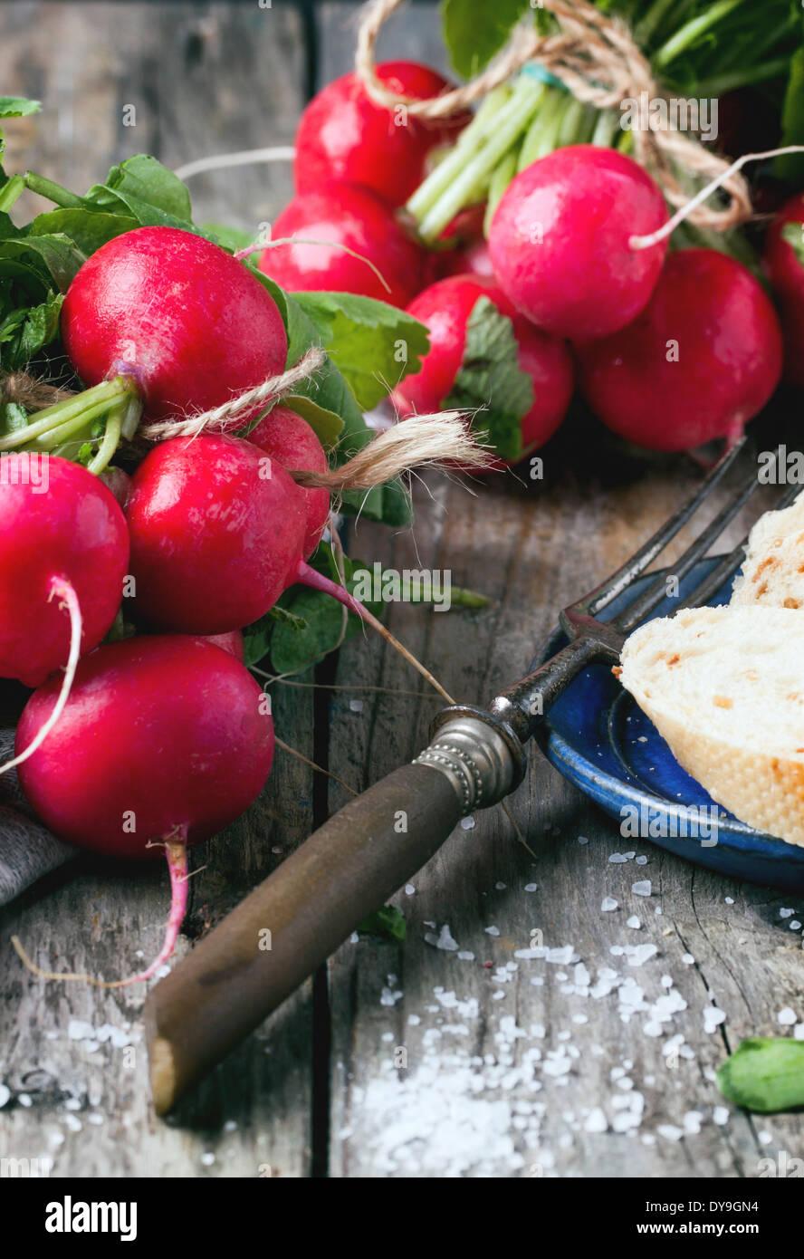 Frisches nass Radieschen mit Vintage Gabel, Meersalz und Brot über alten Holztisch Stockfoto
