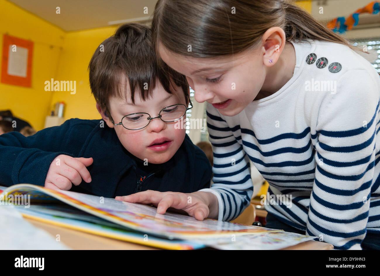 Nicht behinderte und behinderte Schüler (in diesem Fall ein Junge mit Down-Syndrom) lernen gemeinsam in der gleichen Klasse. Stockbild