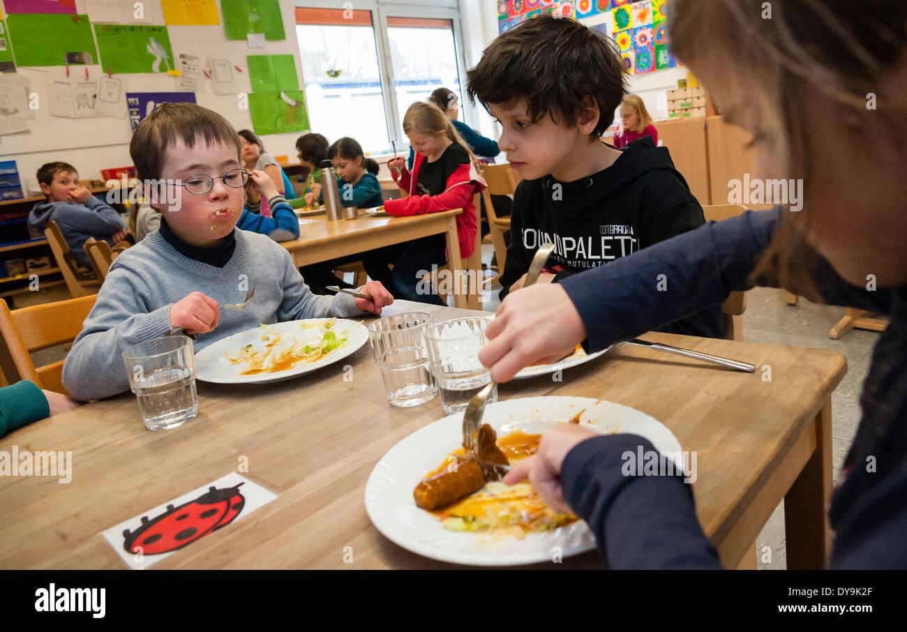 Nicht behinderte und behinderte Schüler (in diesem Fall ein Junge mit Down-Syndrom) haben Mittagessen zusammen in ihrem Klassenzimmer. Stockbild