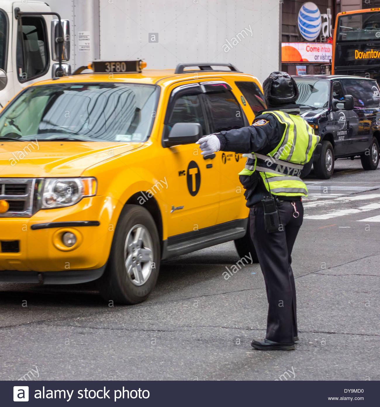 New York Police Department (NYPD) regelt den Verkehr in Manhattan, New York City, mit einem gelben Taxi Stockbild