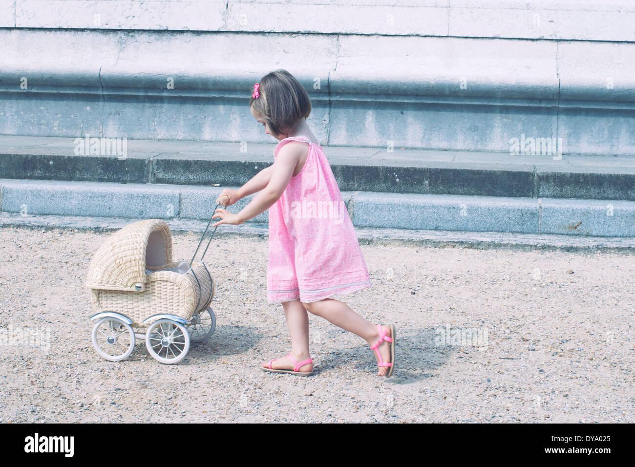 Kleines Mädchen Miniatur Kinderwagen schieben Stockfoto