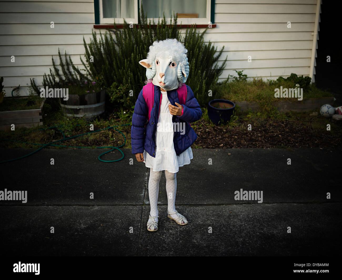 Tag in der Schule verkleiden: Mädchen begibt sich auf den Weg zur Schule, gekleidet wie ein Schaf Stockfoto