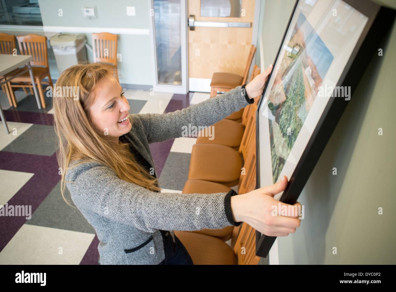 Junge Frau hängen Fotografien an Wand Stockbild