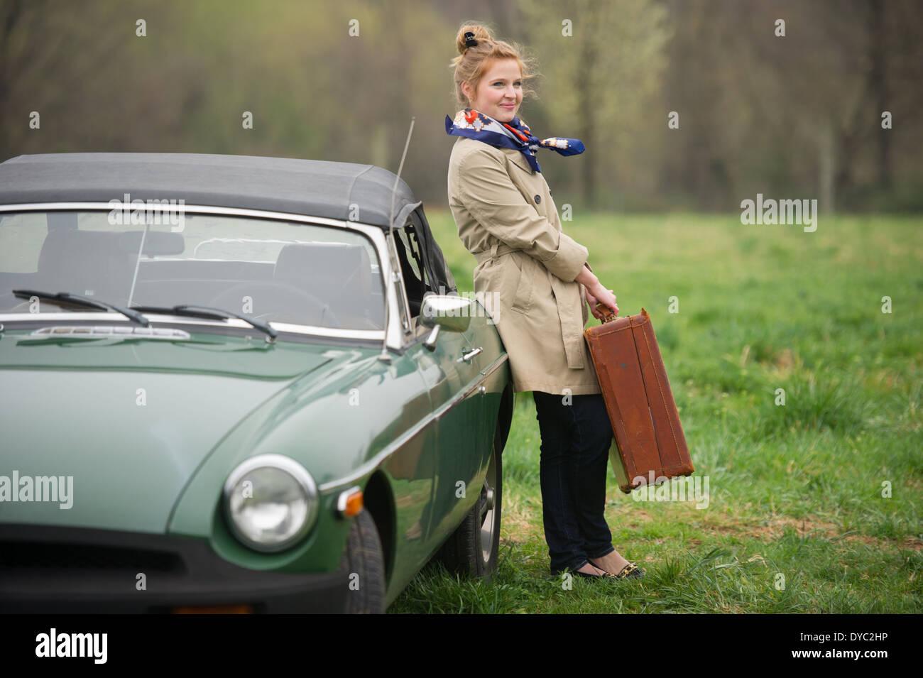 Frau mit gepackten Koffern auf Reise neben klassischen britischen Sportwagen Stockbild
