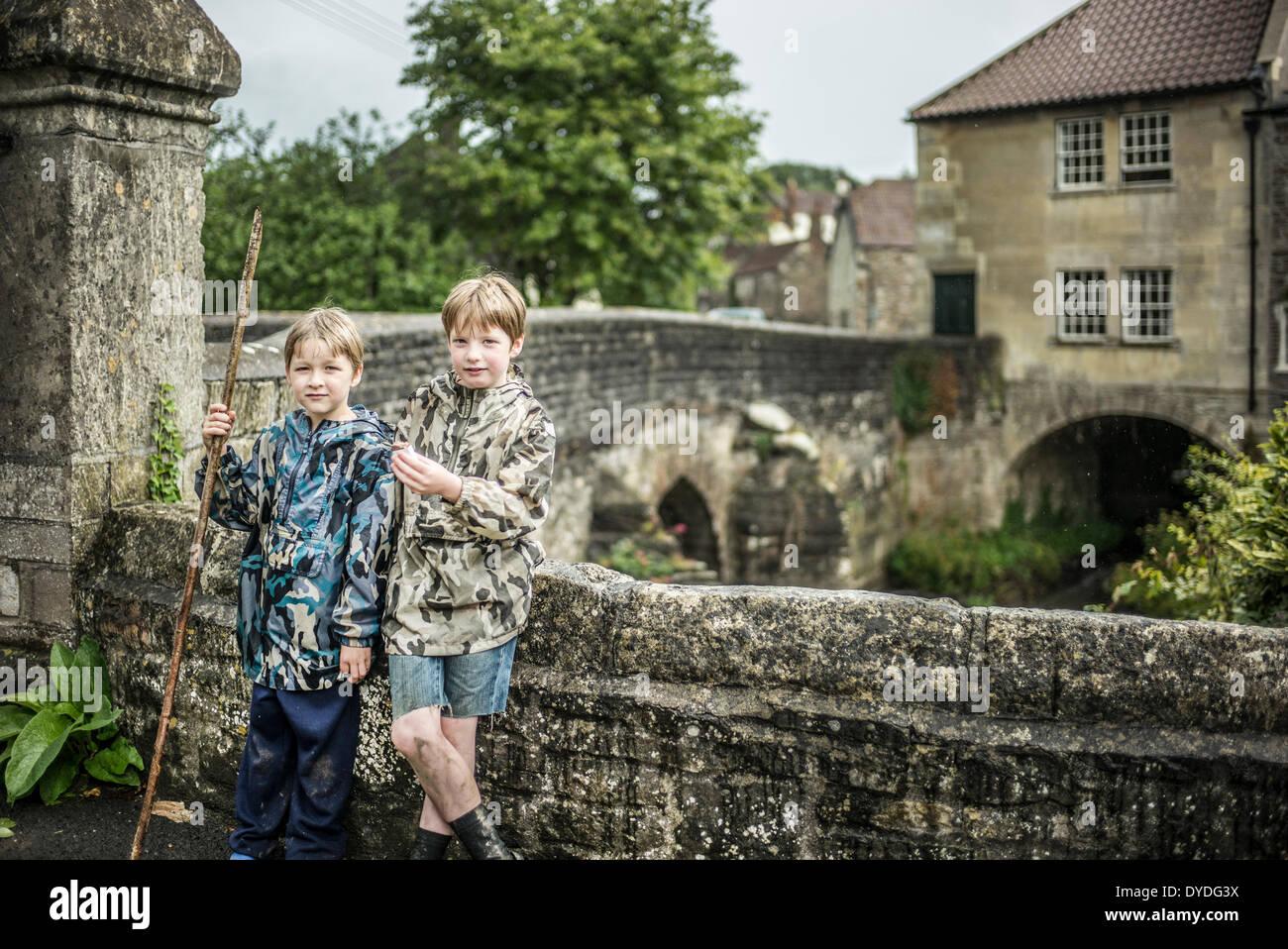 Zwei Brüder stehen neben dem Fluss Chew an Pensford Brücke in Somerset. Stockbild
