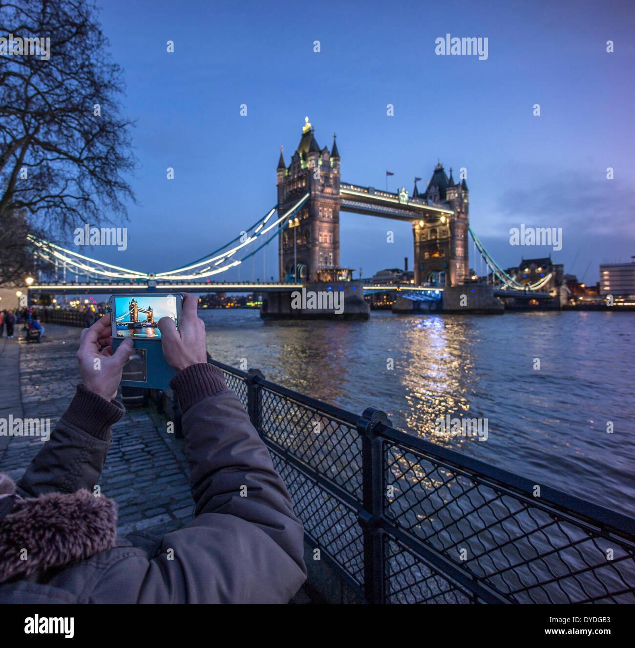 Ein männlichen Touristen nimmt ein Bild auf die Tower Bridge bei Nacht von der Nordseite. Stockfoto