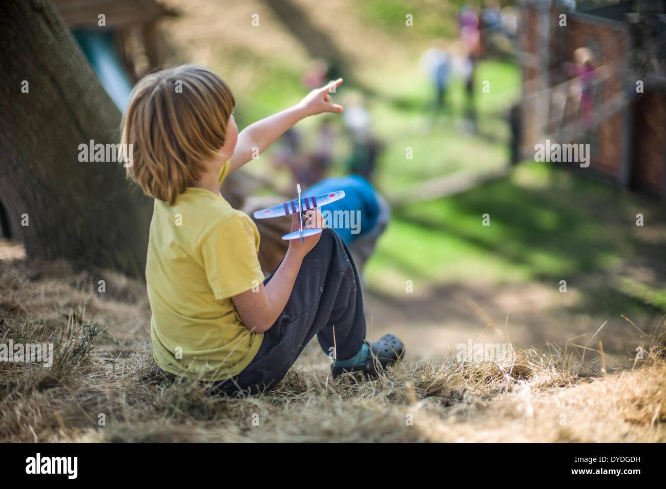 Ein kleiner Junge mit einem Spielzeugflugzeug zu Hatfield House Abenteuerspielplatz spielen. Stockbild