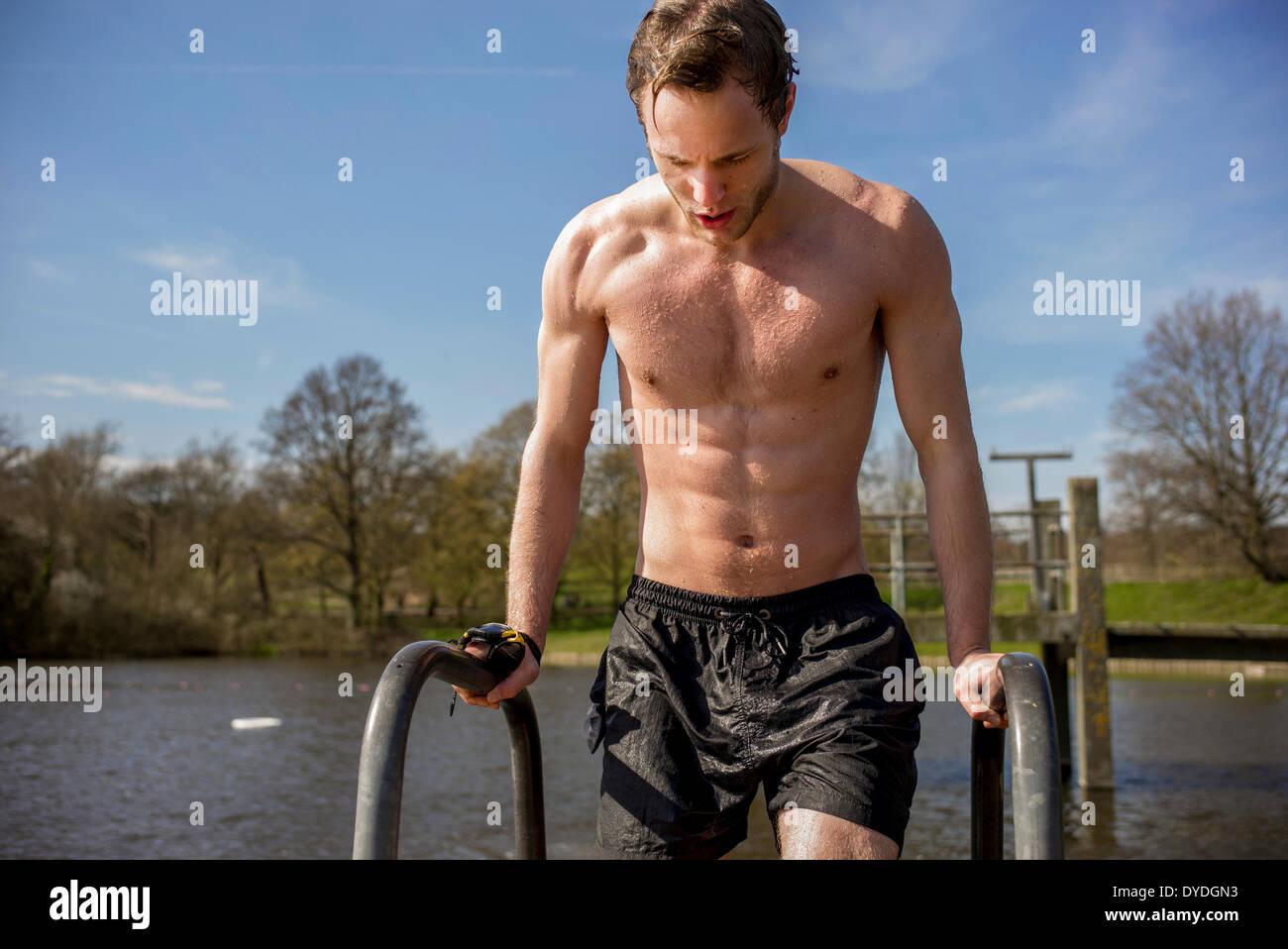 Ein junger Mann in Badehose neben Frühjahr frisches Wasserteiche. Stockbild