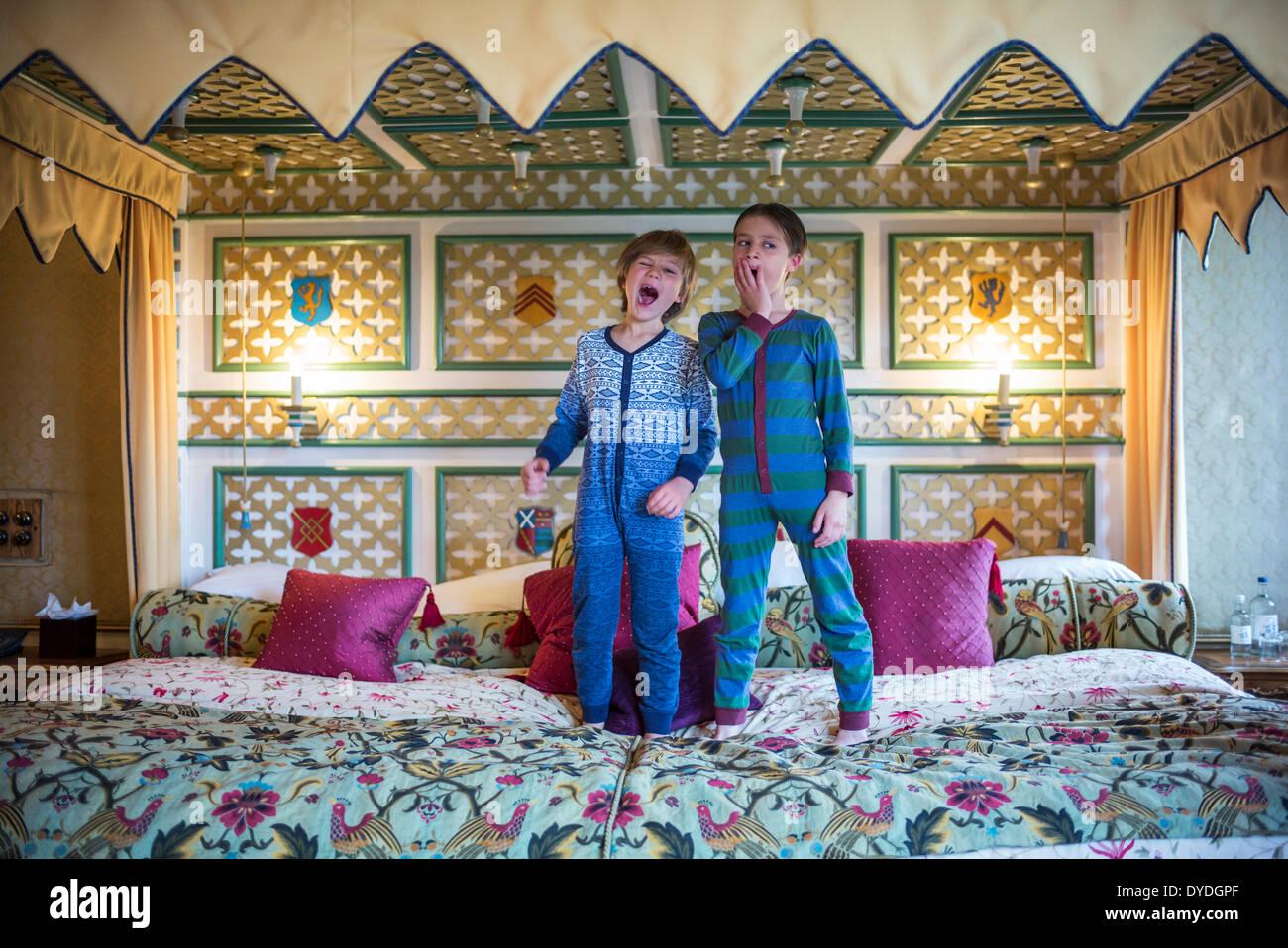 Zwei Jungs Gähnen im Onesies auf dem größten Hotelbett in Europa in Thornbury Castle. Stockbild