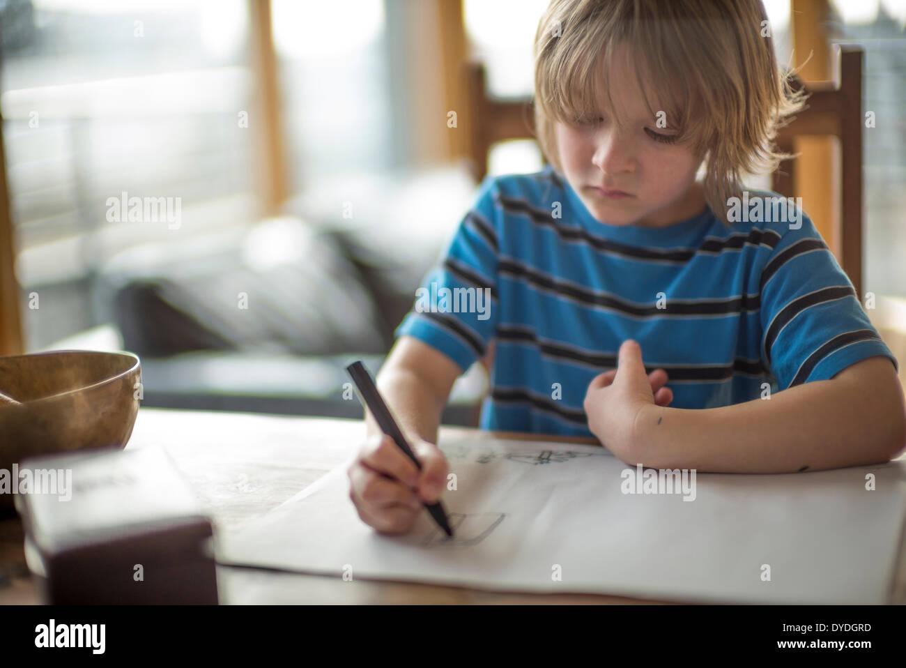 Sieben Jahre alter Junge Zeichnung am Tisch. Stockbild