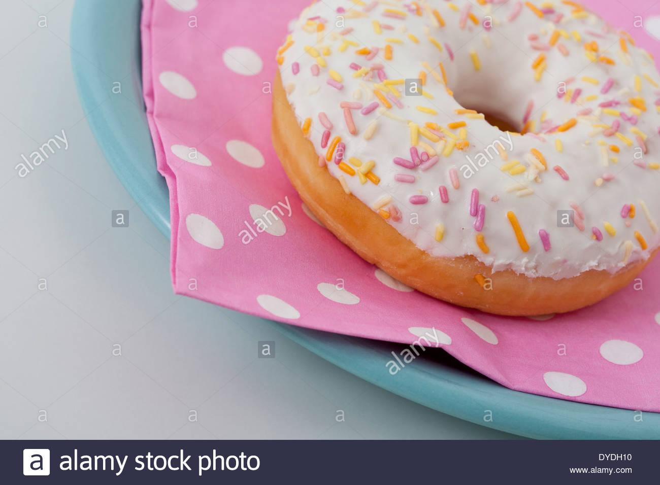 Nahaufnahme von Donut mit Zuckerguss und bunte Streusel auf fleckig rosa Serviette auf Platte auf hellem Hintergrund Stockbild