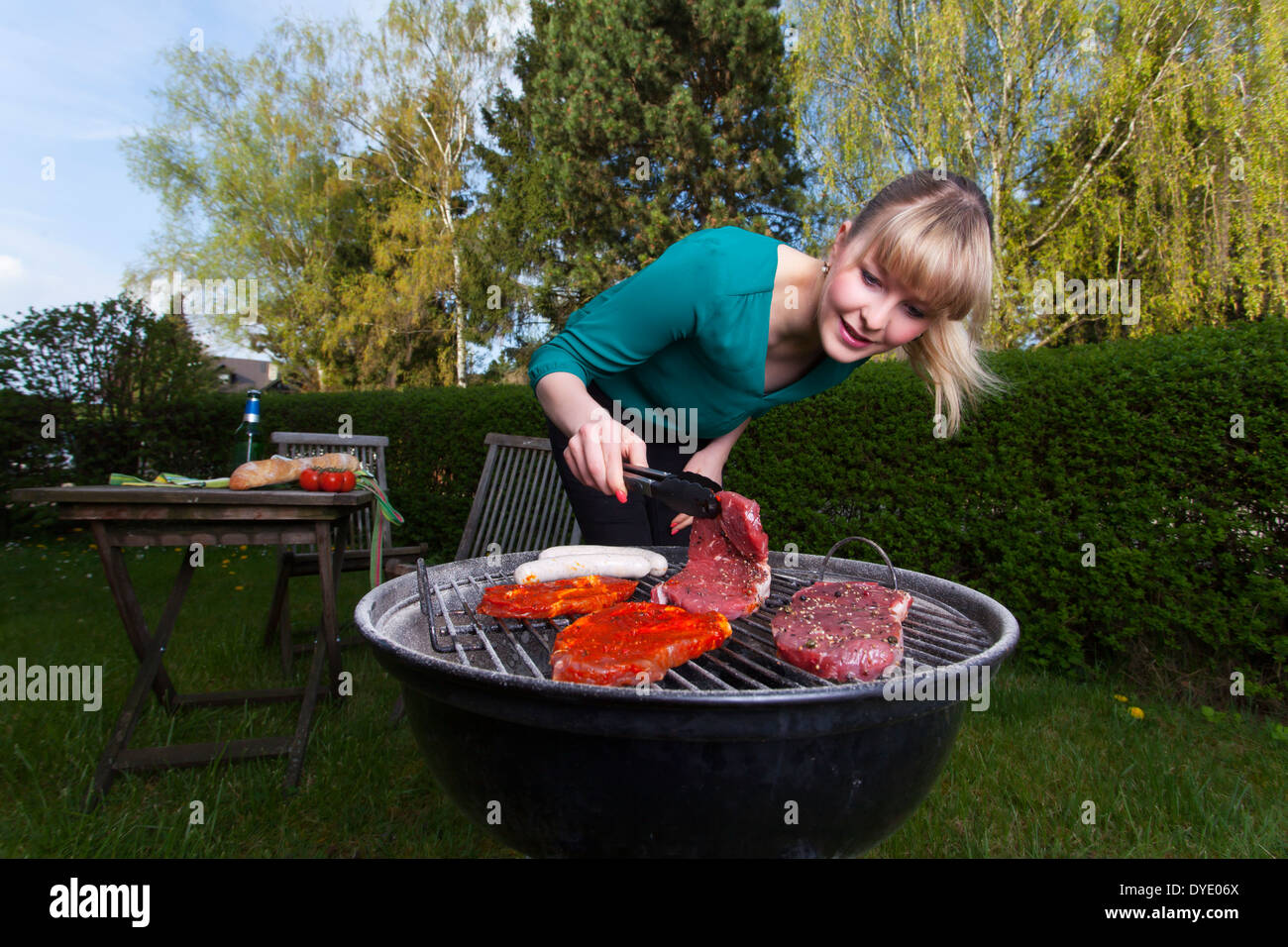 Frau und ein Grill Stockbild