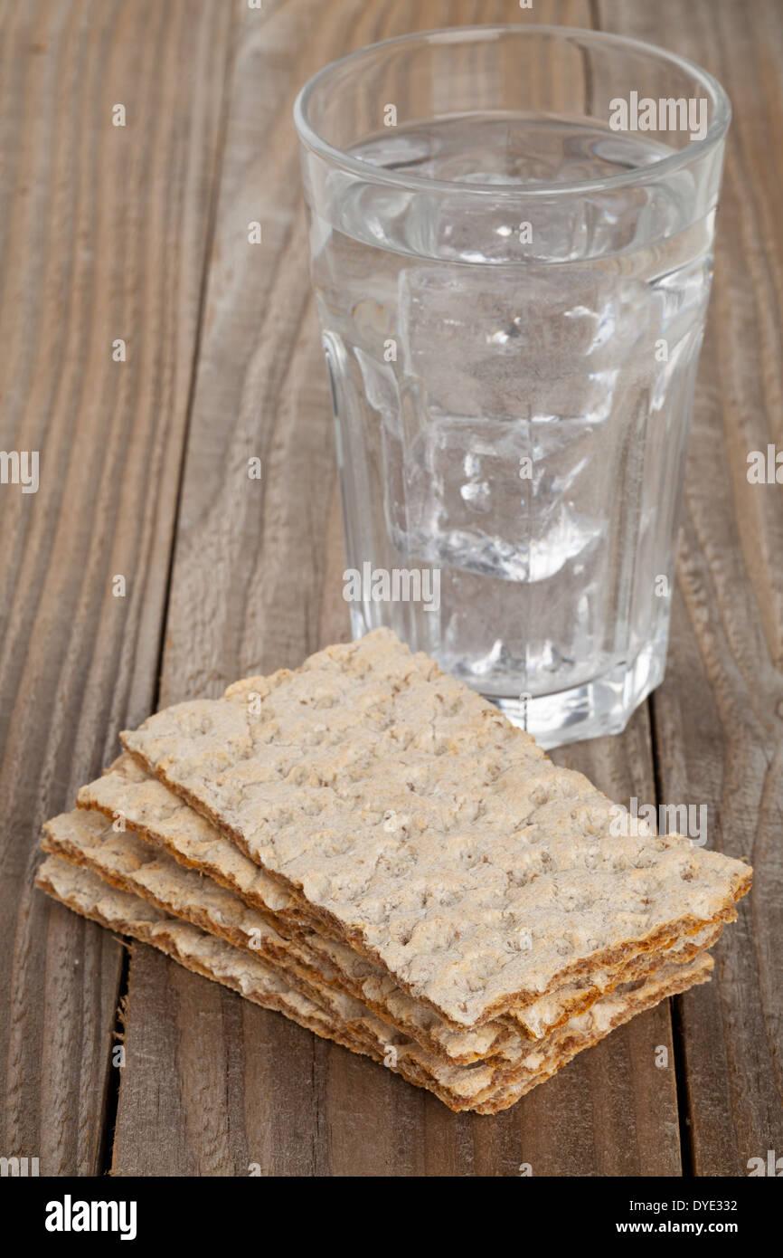 Gestapelte Scheiben Weizen Knackebrot Mit Glas Wasser Auf Holztisch