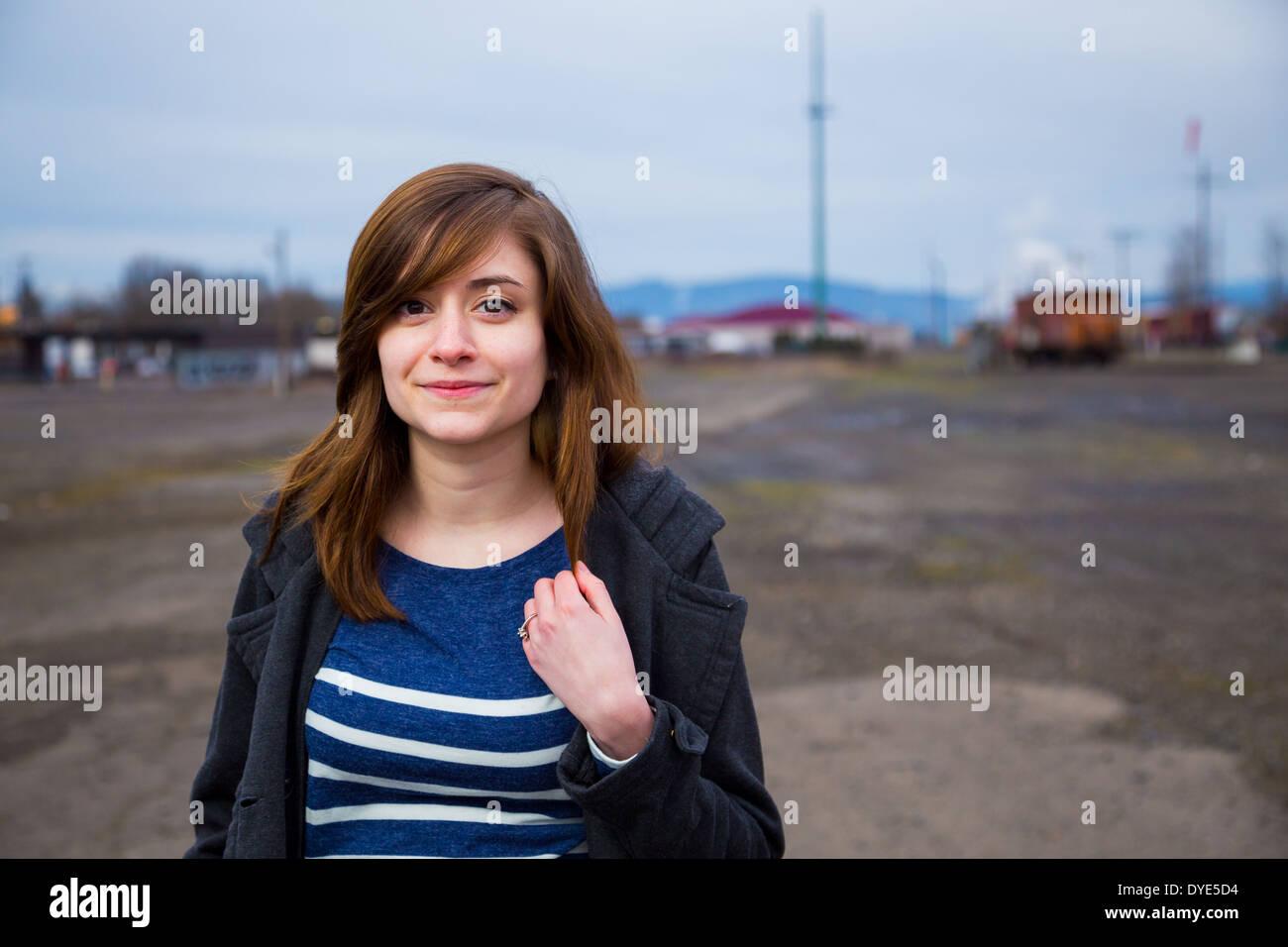 Moderne, trendige, hipster Girl in einem verlassenen Bahnhof Hof bei Dämmerung in diesem Mode Stil portrait. Stockbild