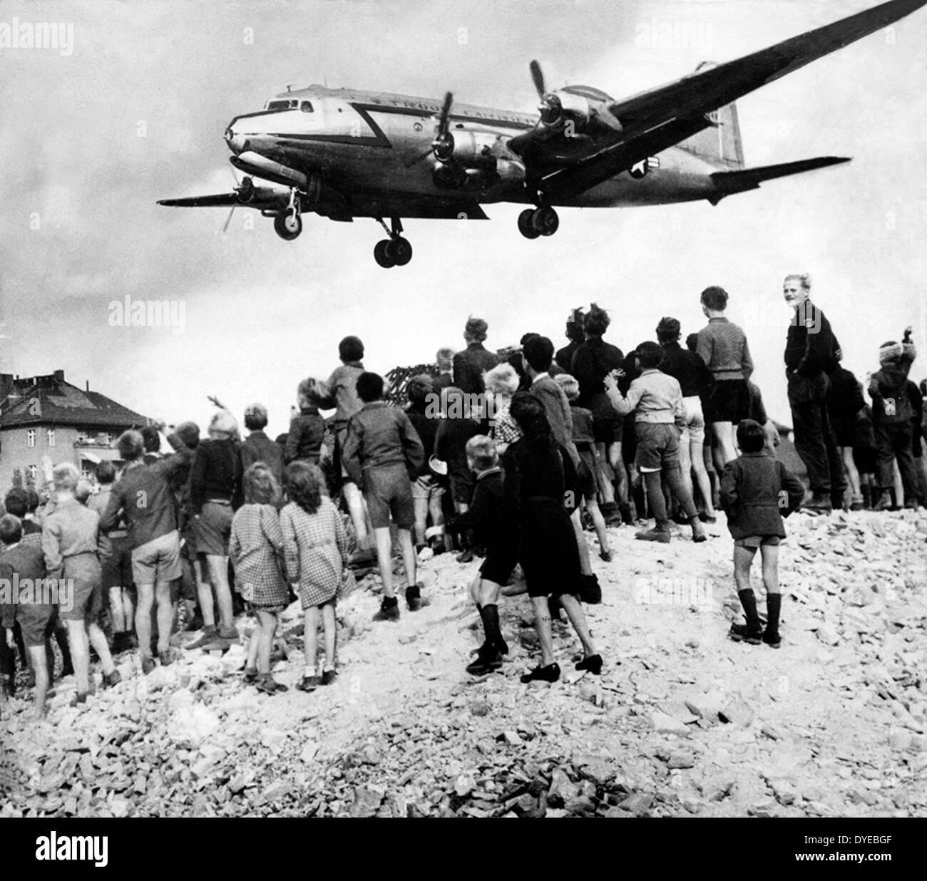 Amerikanische Flugzeuge fällt Nahrung und liefert in der Nähe von einer Schar von Berliner während der Berlin-blockade Stockbild