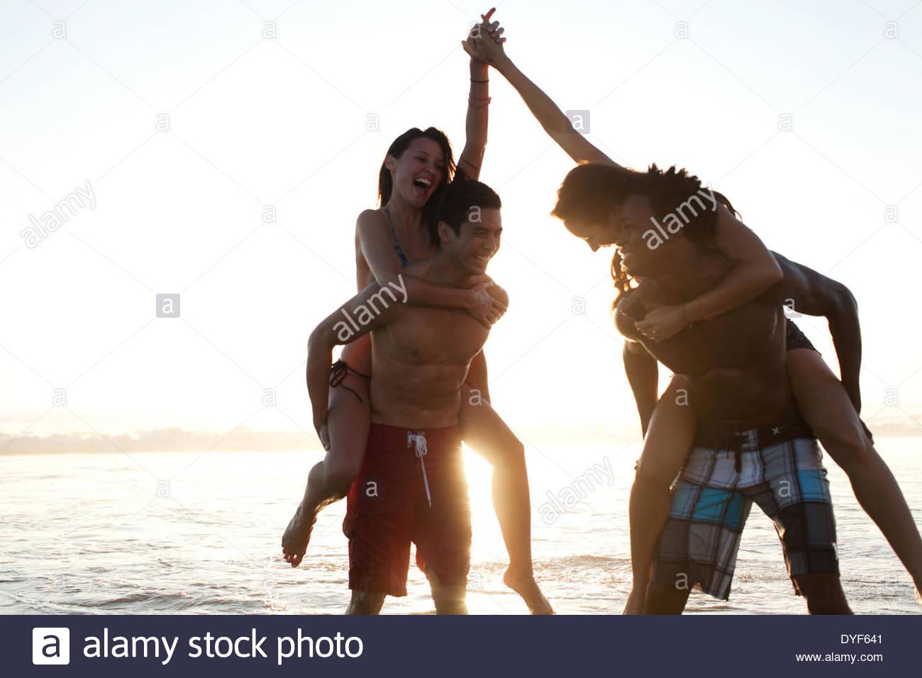 Paare spielen in Wellen am Strand Stockbild