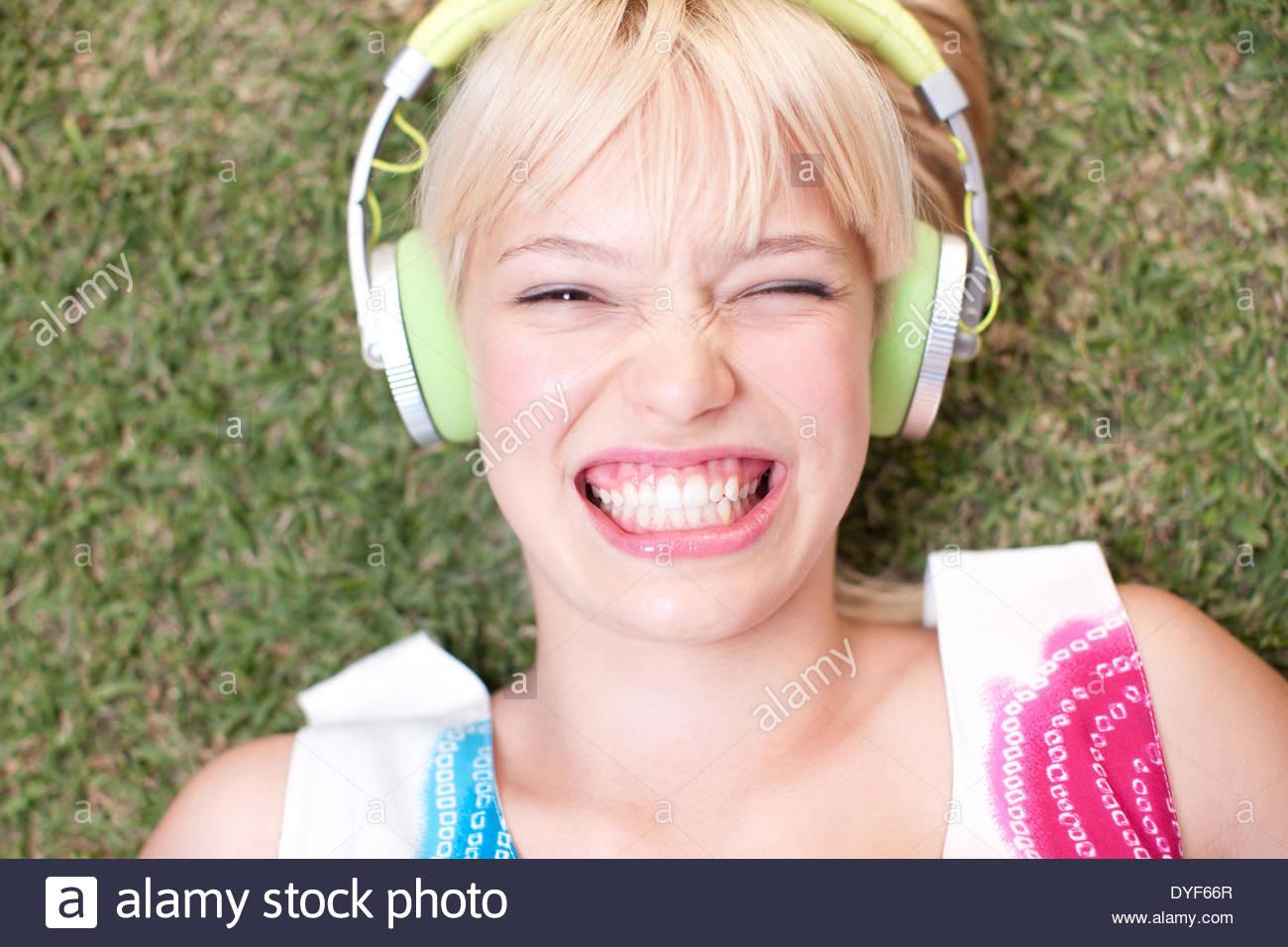 Frau, die Verlegung auf dem Rasen Kopfhörer anhören Stockbild