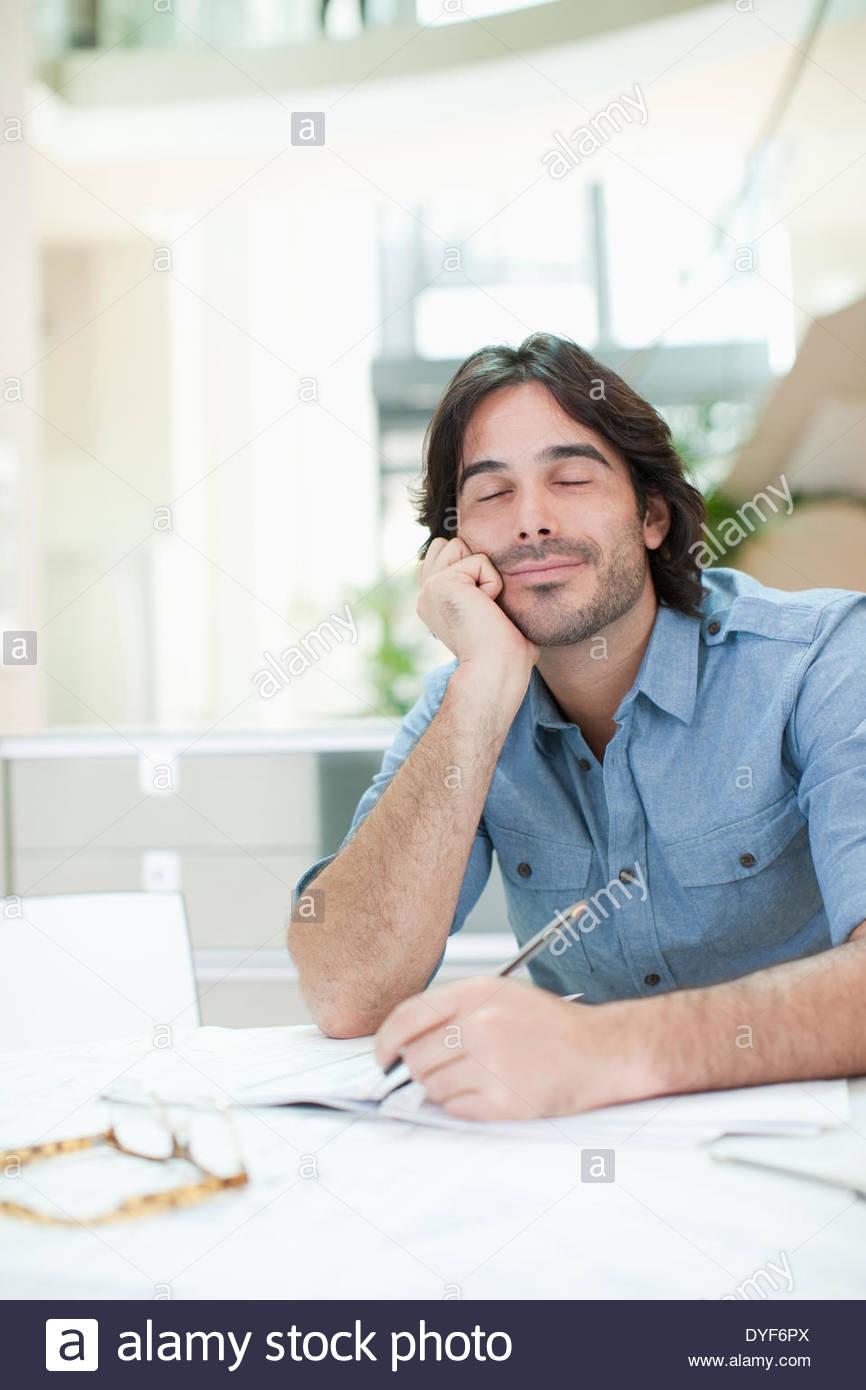 Geschäftsmann, träumen am Schreibtisch im Büro Stockbild