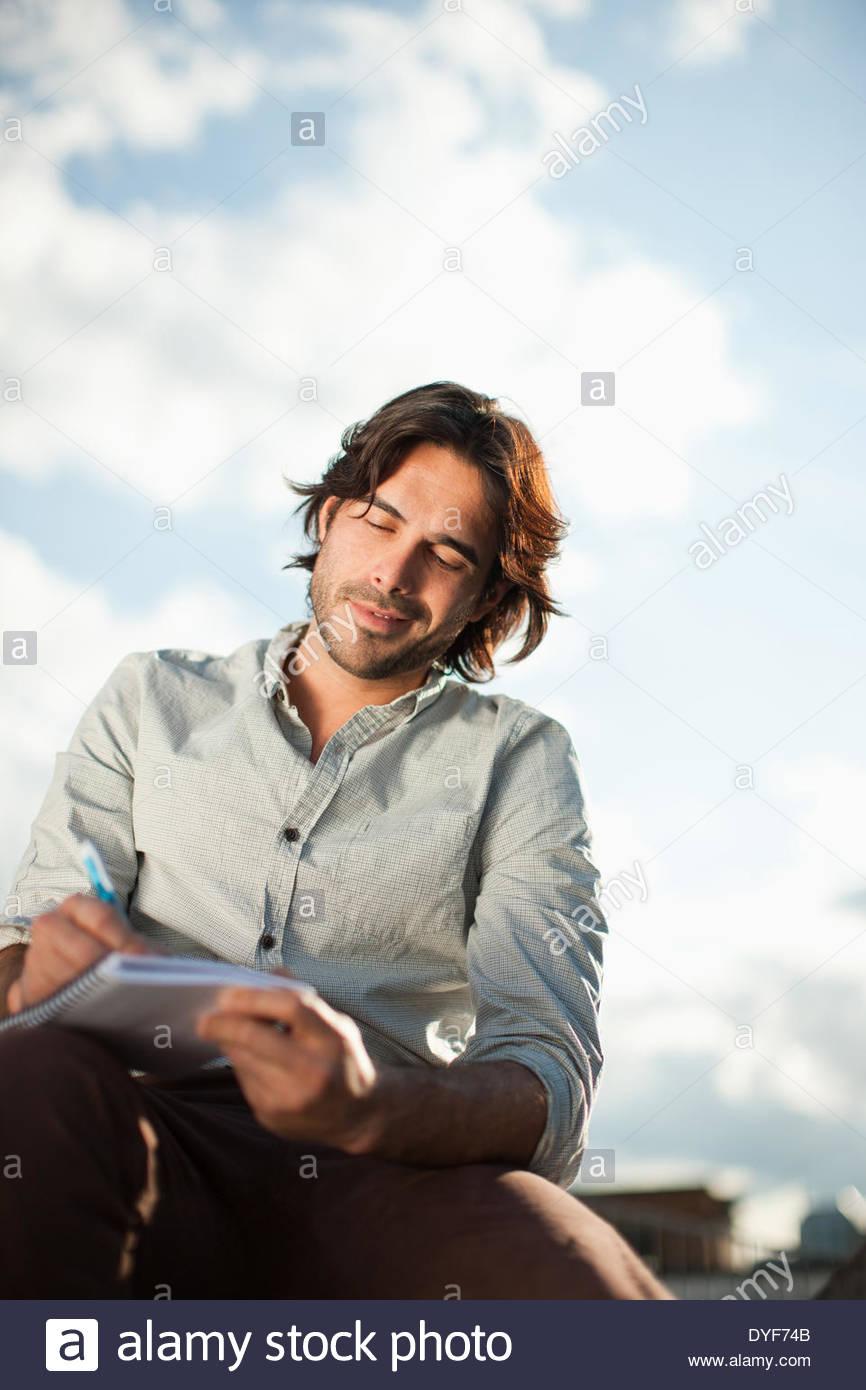 Nachdenklich Geschäftsmann schreiben in Notebook im freien Stockbild