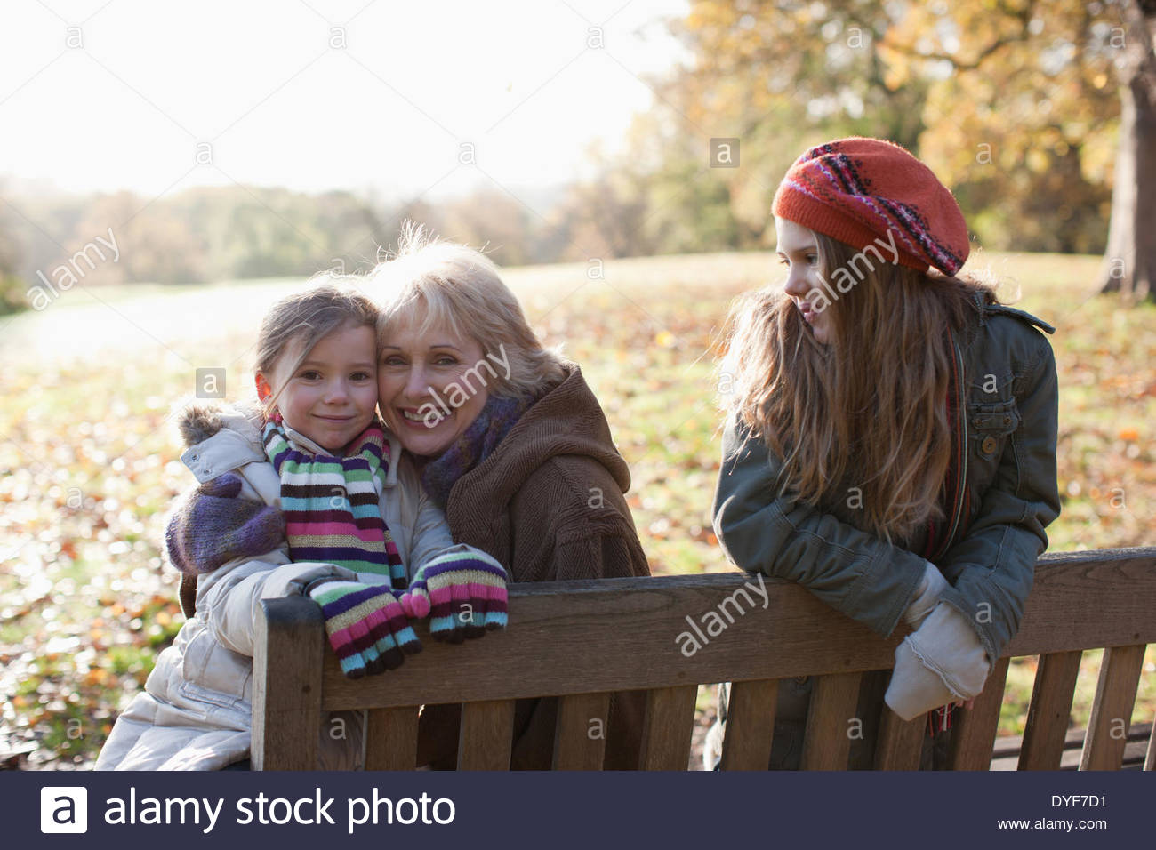 Großmutter umarmt Enkelin im freien Stockbild